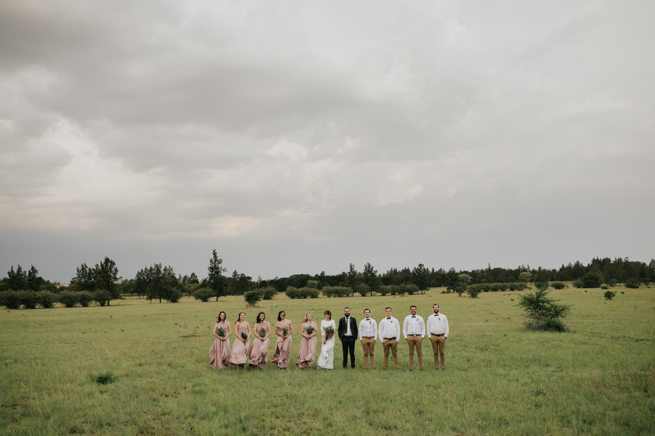 Wide epic bridal party photo in an open farm field