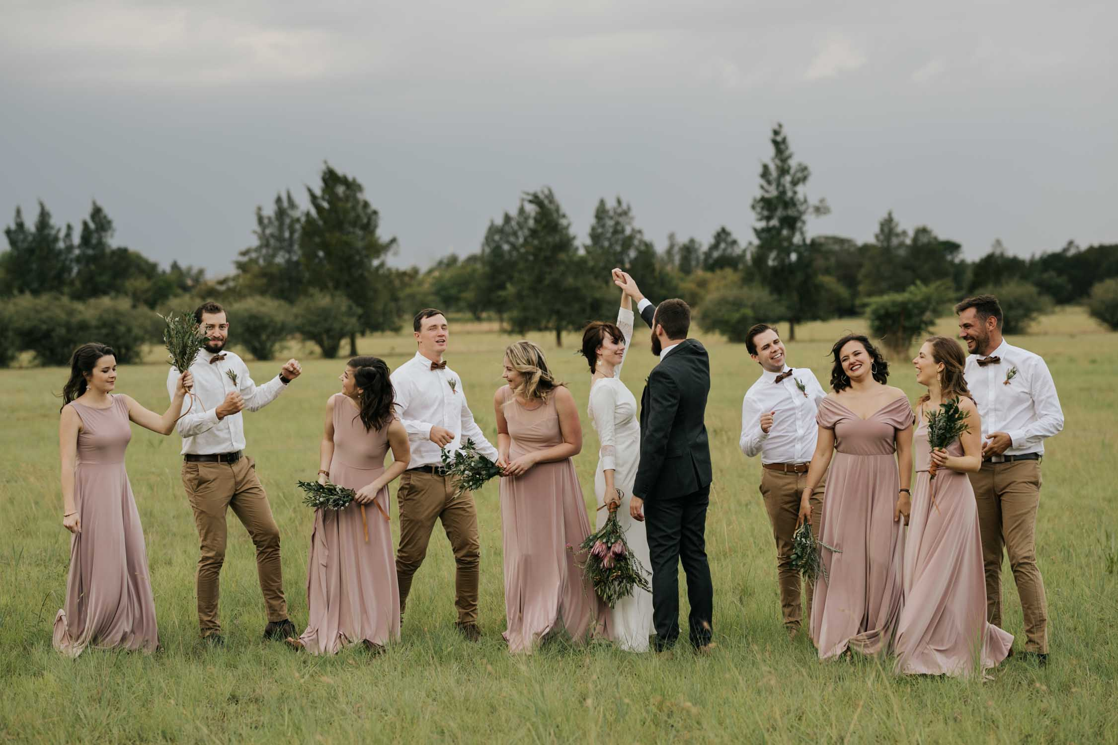 Fun different natural retinue photo of bridal party dancing together in a field