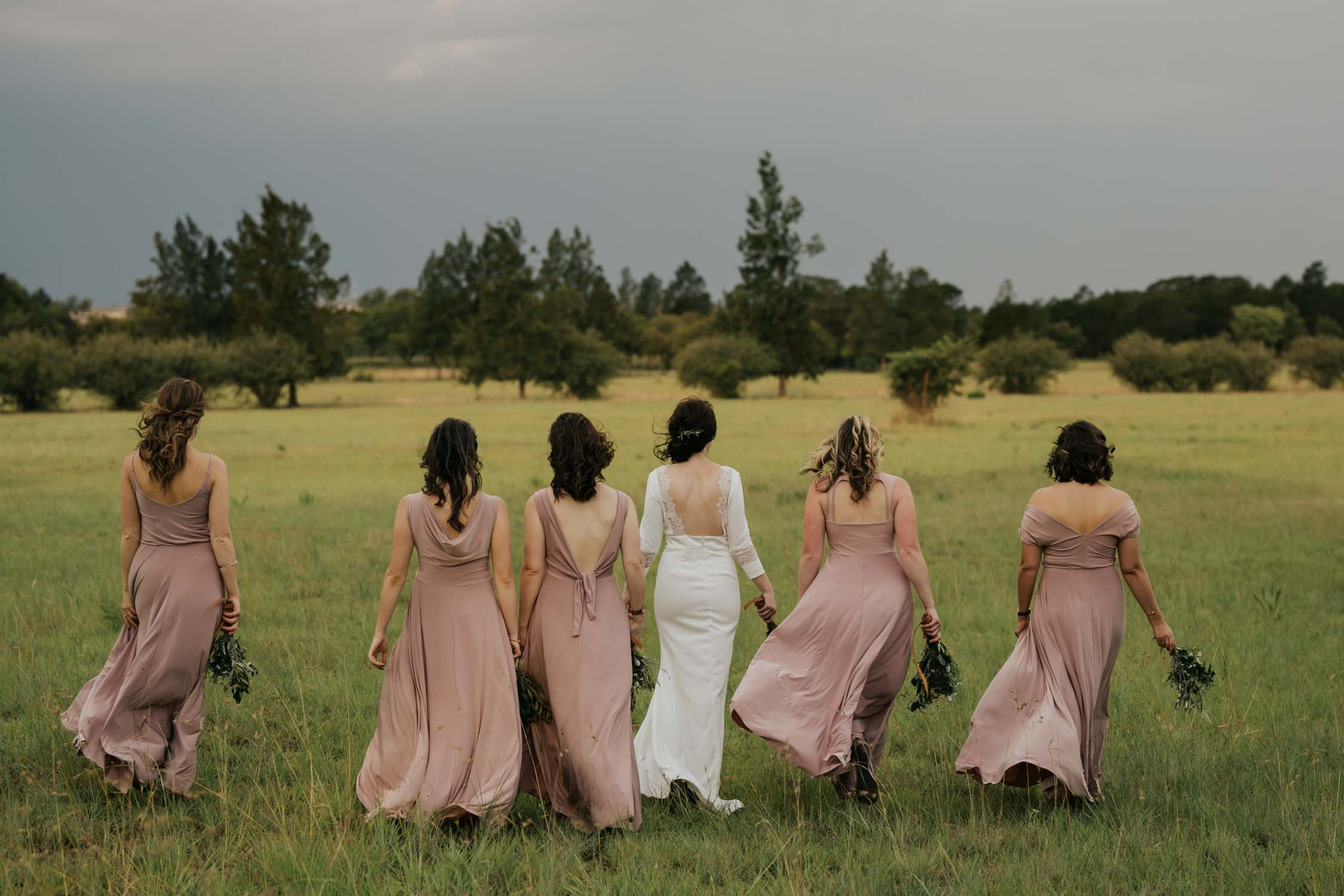 Natural photo of bride and bridesmaids walking together in a farm field