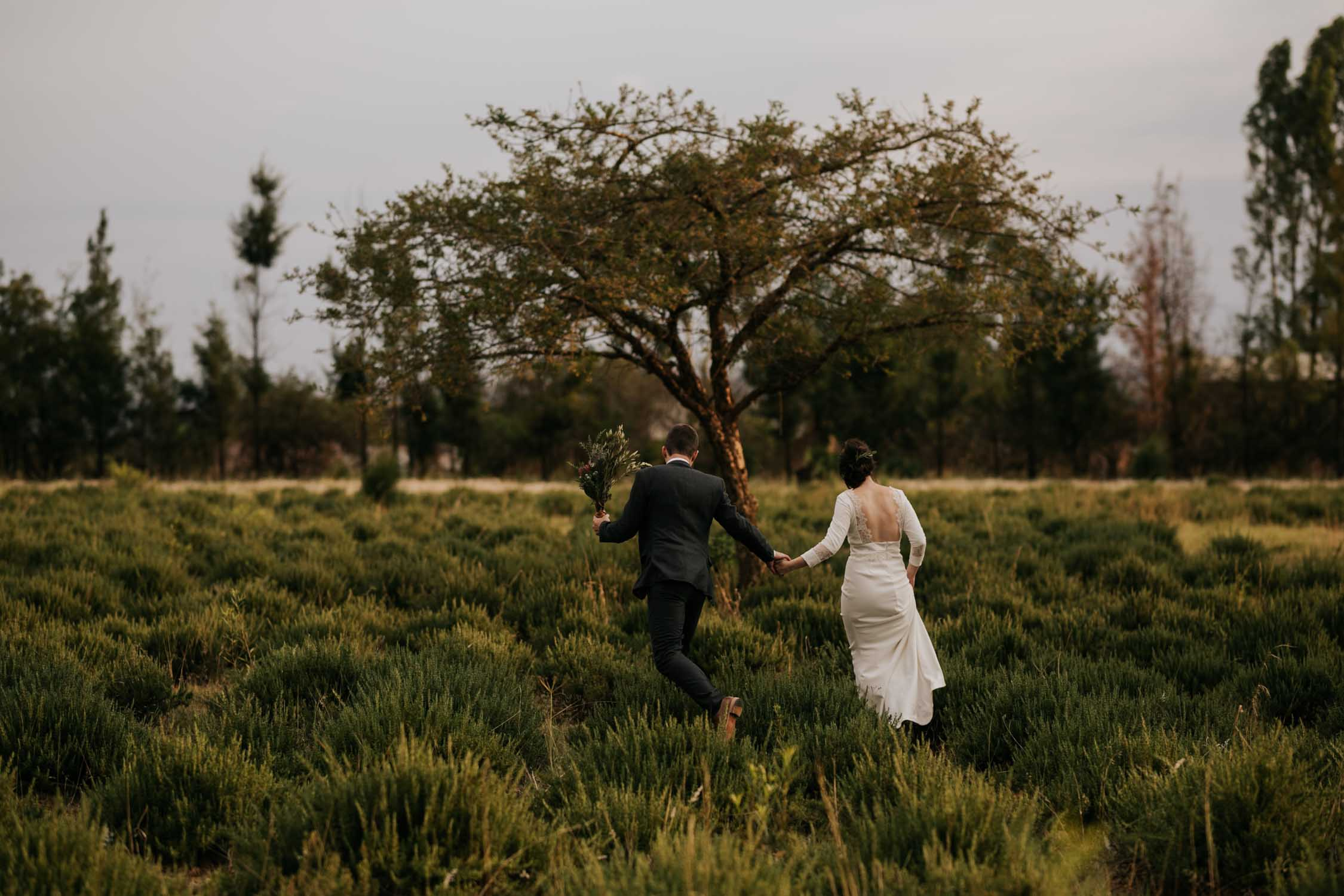 Happy and fun photo of bride and groom running through a field taken by photojournalistic Vancouver Wedding Photographer