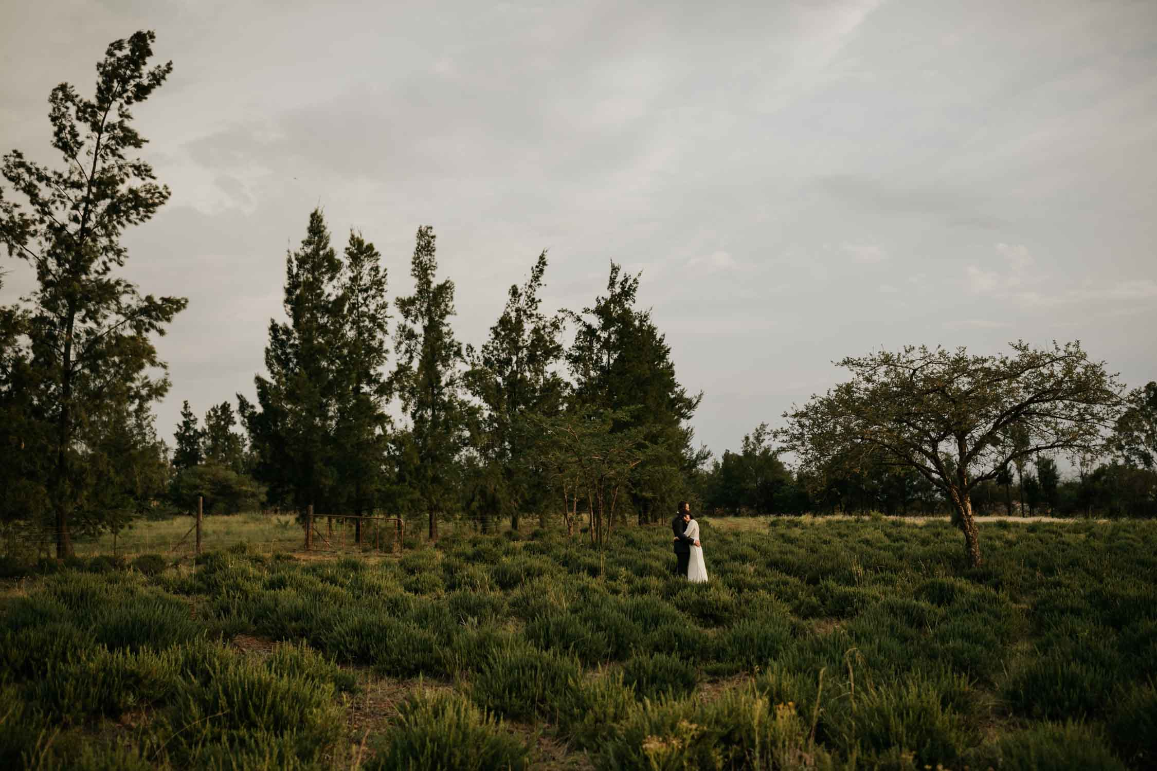 Wide landscape photo with couple in the middle of the farm field holding each other captured by best Vancouver Wedding Photographer