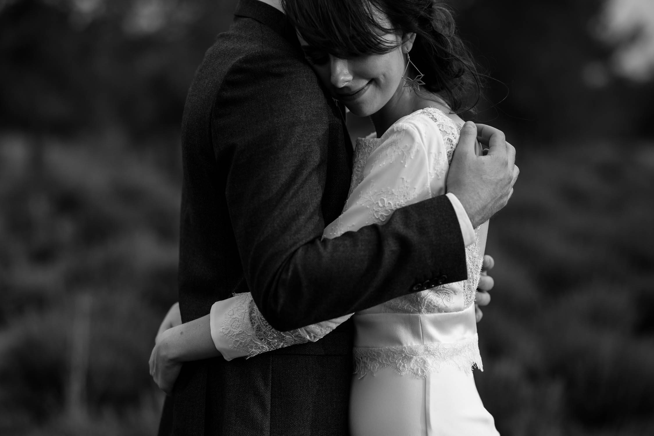 Black and white photojournalistic photo of bride with natural bridal upstyle putting her head on groom's shoulder