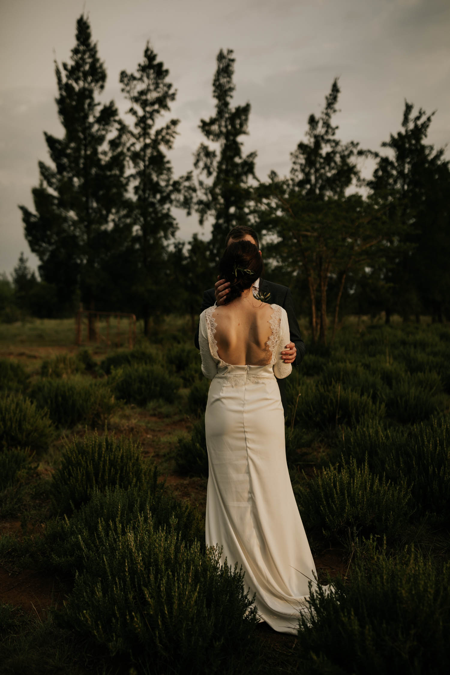 Non cheesy and Intimate moment of groom holding bride showing off her gorgeous open back lace wedding dress taken by Vancouver Wedding Photographer