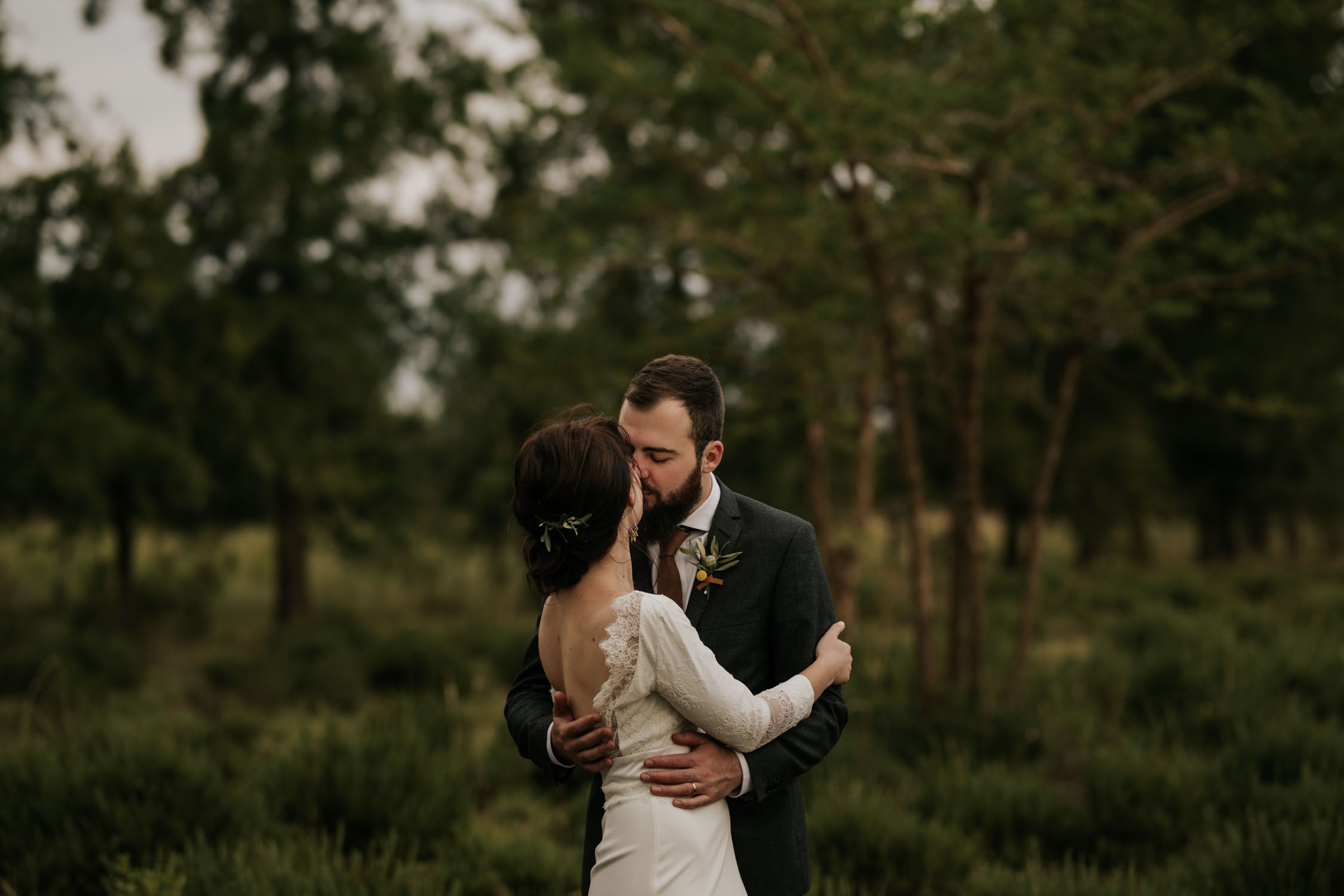 Spontaneous moment captured of groom kissing bride in forest