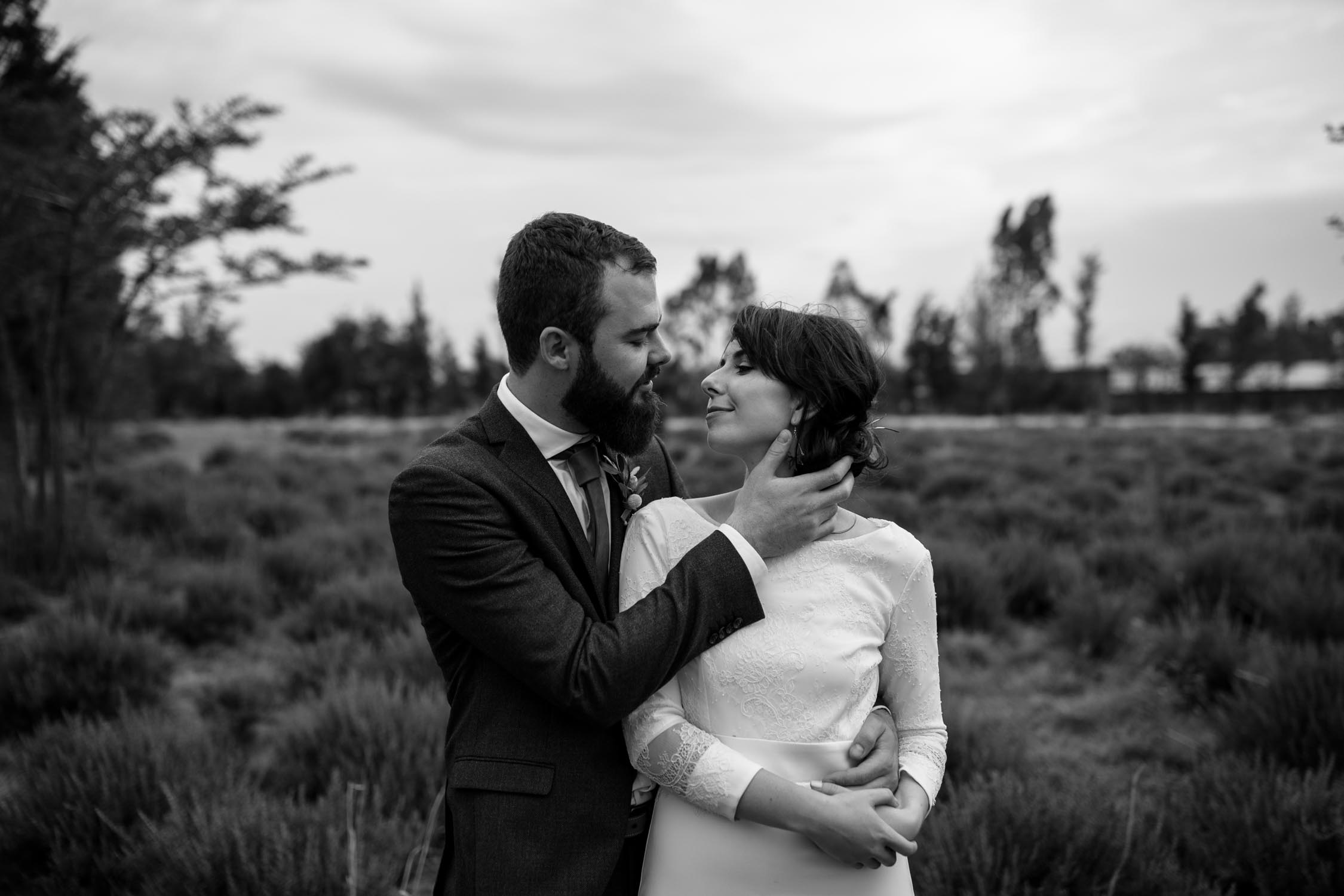 Newlyweds look into each other's eyes and share a quiet moment in rosemary field
