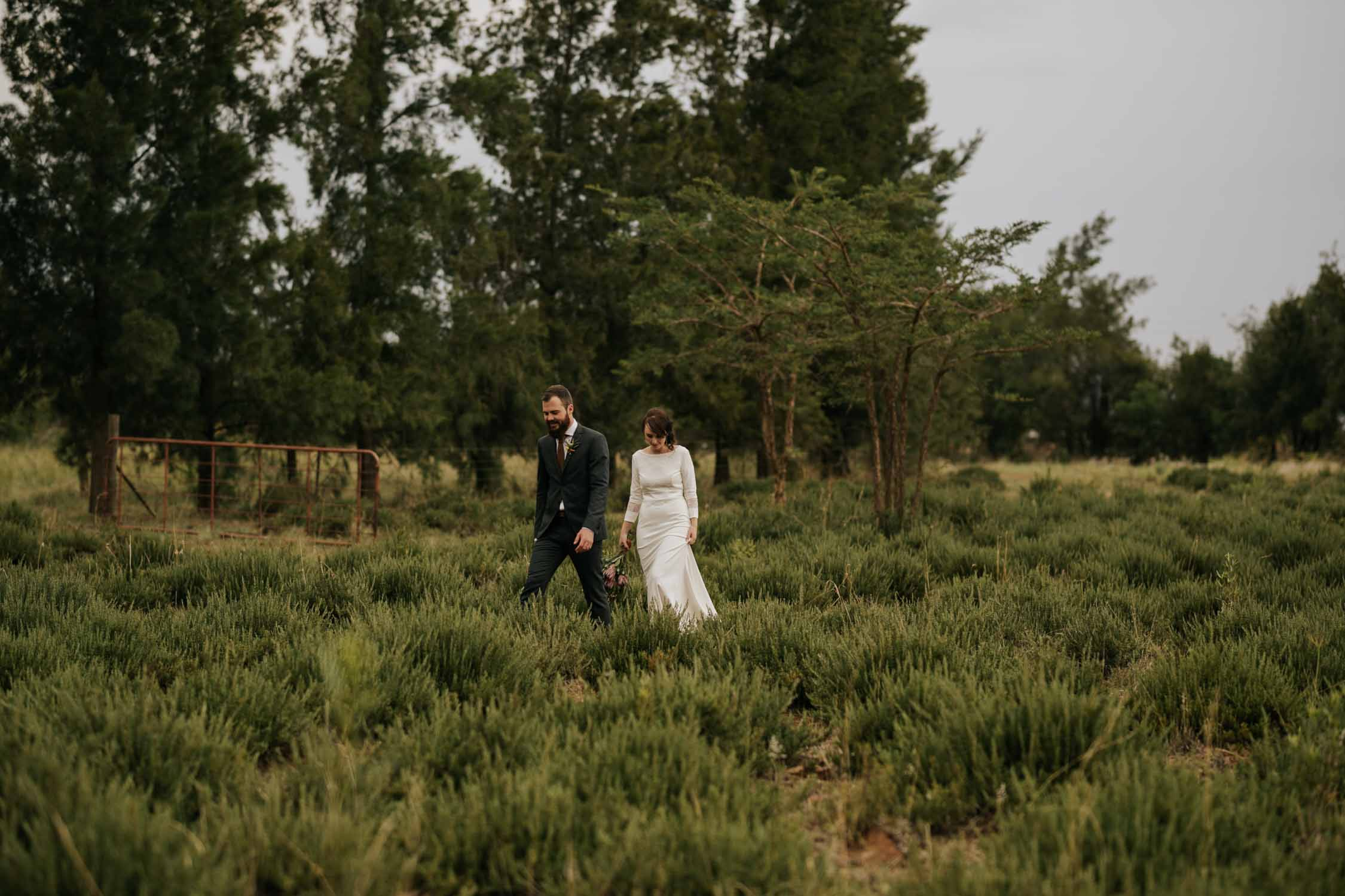 Gorgeous natural groom and bride walk through farm fields and forest at North Vancouver Wedding