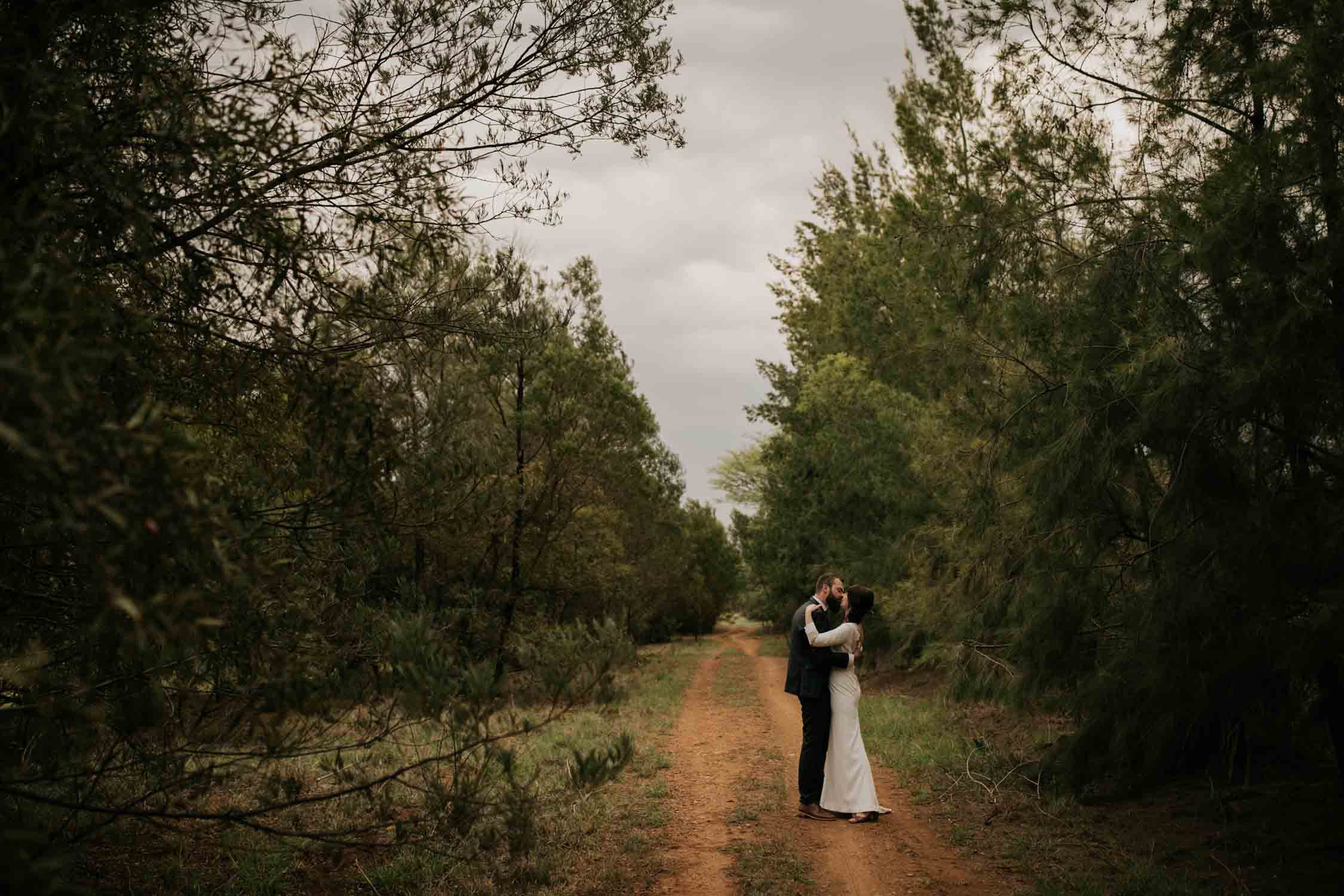 Bride and groom kiss on dusty farm road at Vancouver Island Wedding Venue