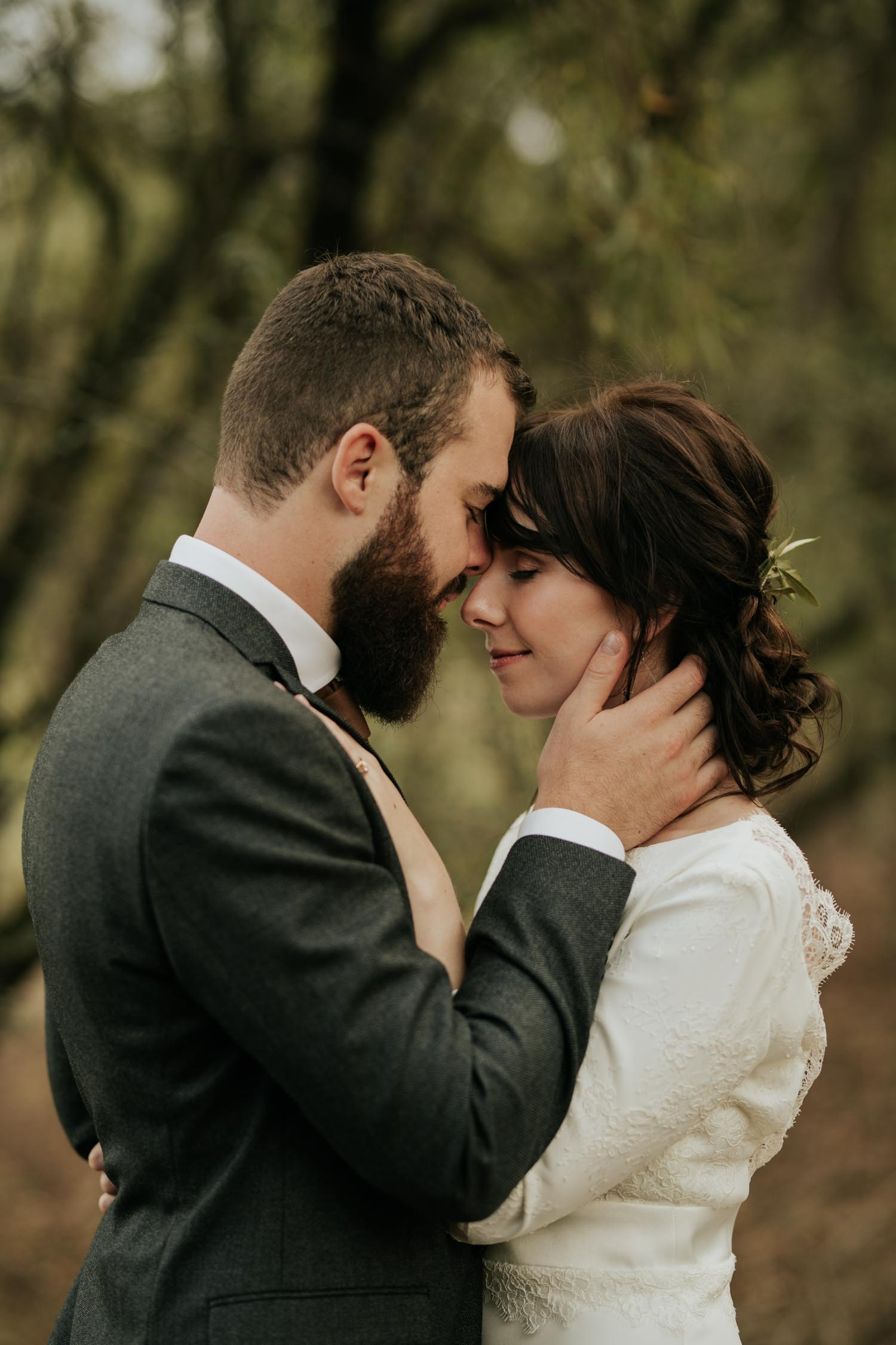 Bride and groom put foreheads together in beautiful forests of Rice Lake, Vancouver, BC