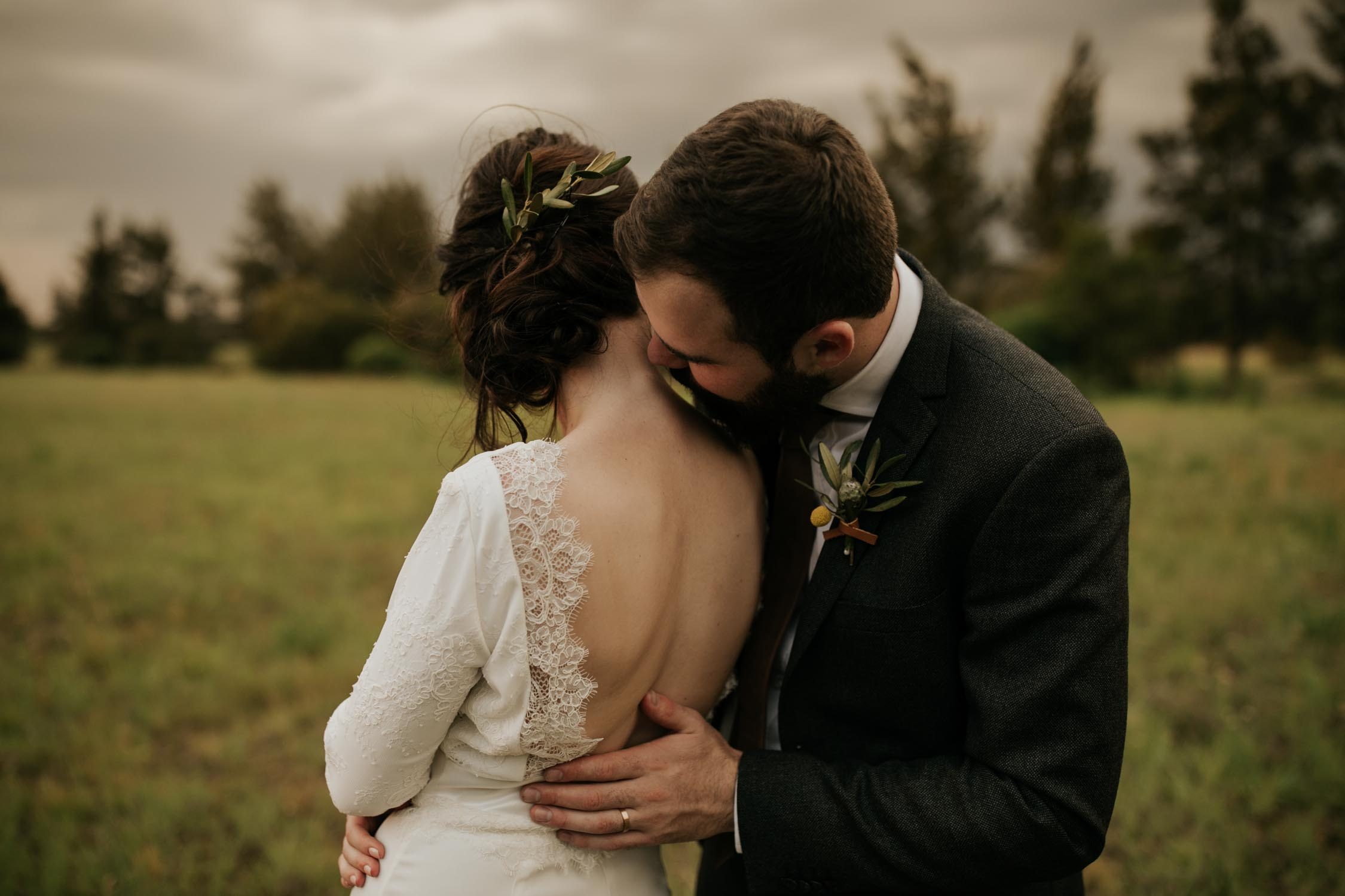Bride wears open back lace lined dress with rosemary sprig in her upstyle natural bridal hair