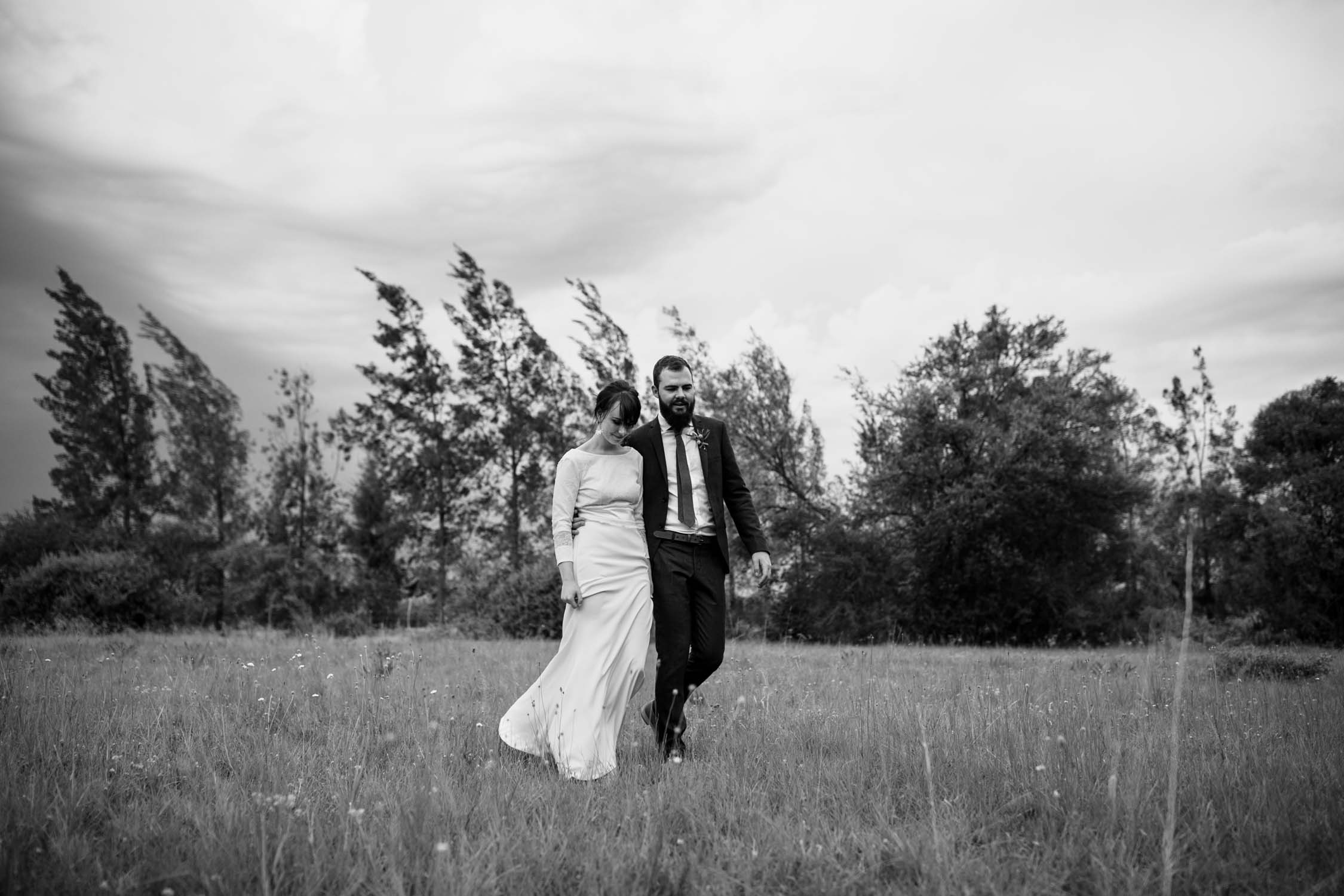 Photo of bride and groom walk in flower field in Spring wedding at Stanley Park taken by best BC Wedding Photographer