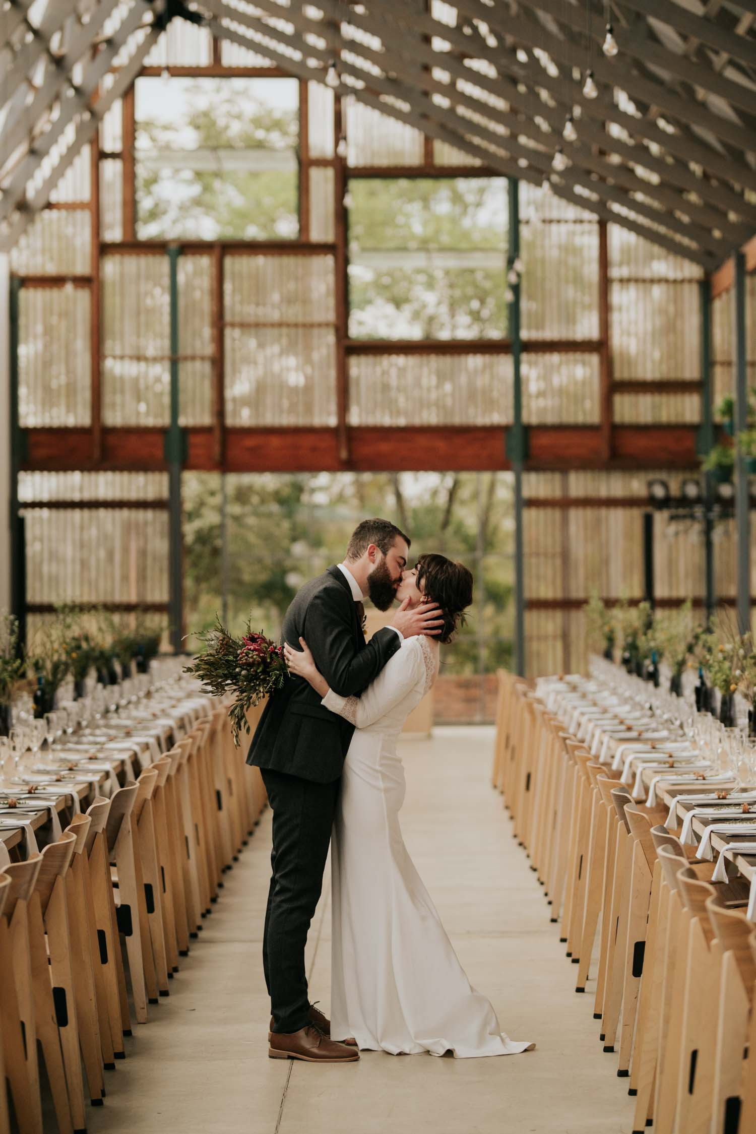 Bride and groom kiss in Scandi style modern and Industrial Wedding Venue in South Africa