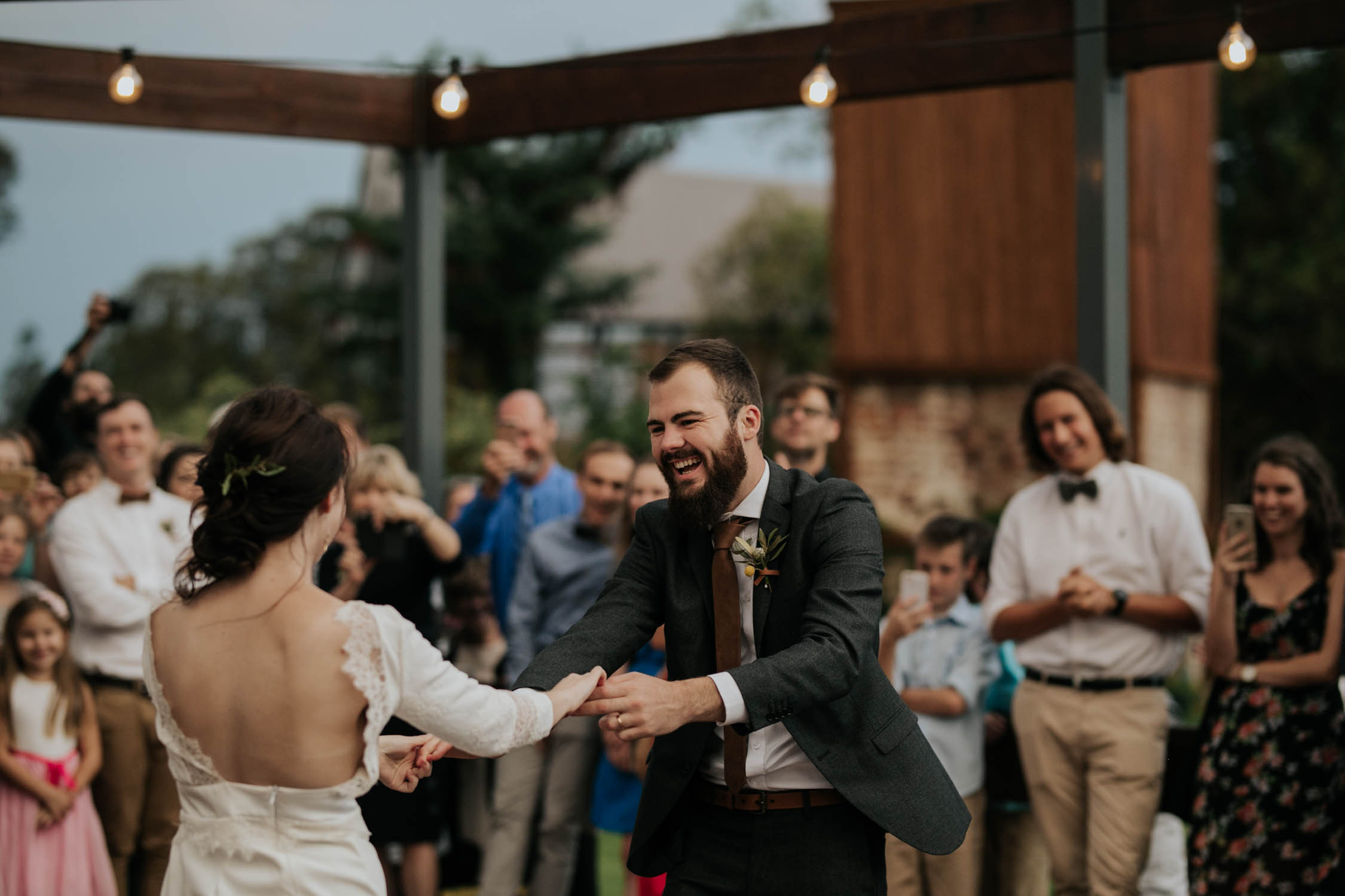 Candid moment of bride and groom's first dance under stars surrounded by wedding guests under Edison light bulbs to live hipster band