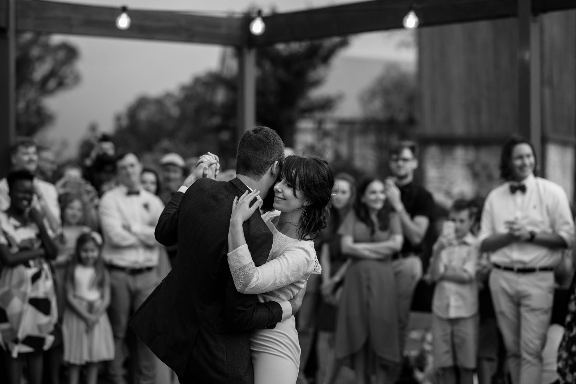 Epic black and white photo of first dance at dusk surrounded by wedding guests under Edison light bulbs to live hipster band