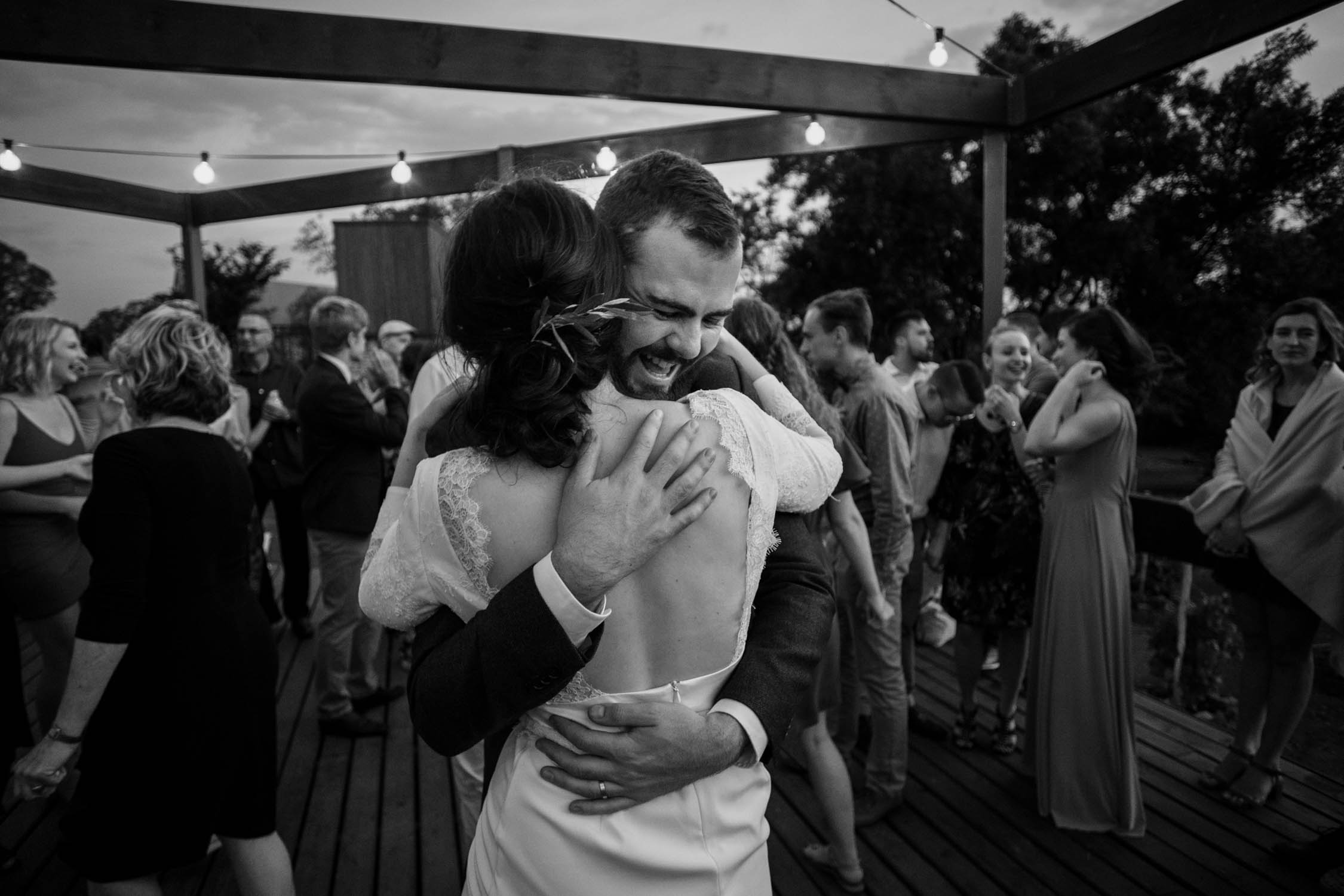 Amazing photo of groom laughing and hugging his new life on the dance floor under the stars