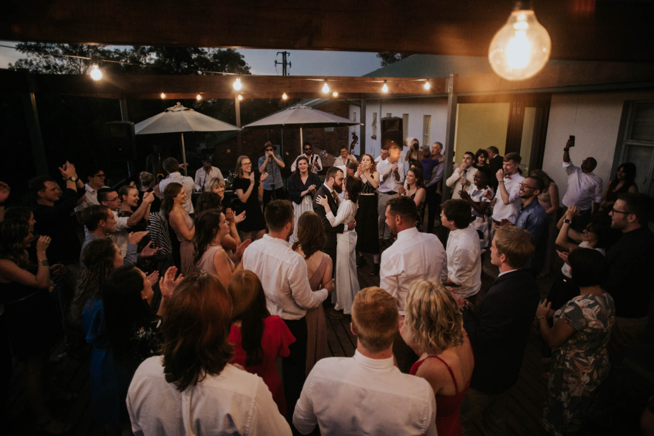 Groom and bride kiss in the middle of the outside dance floor while family and friends cheer