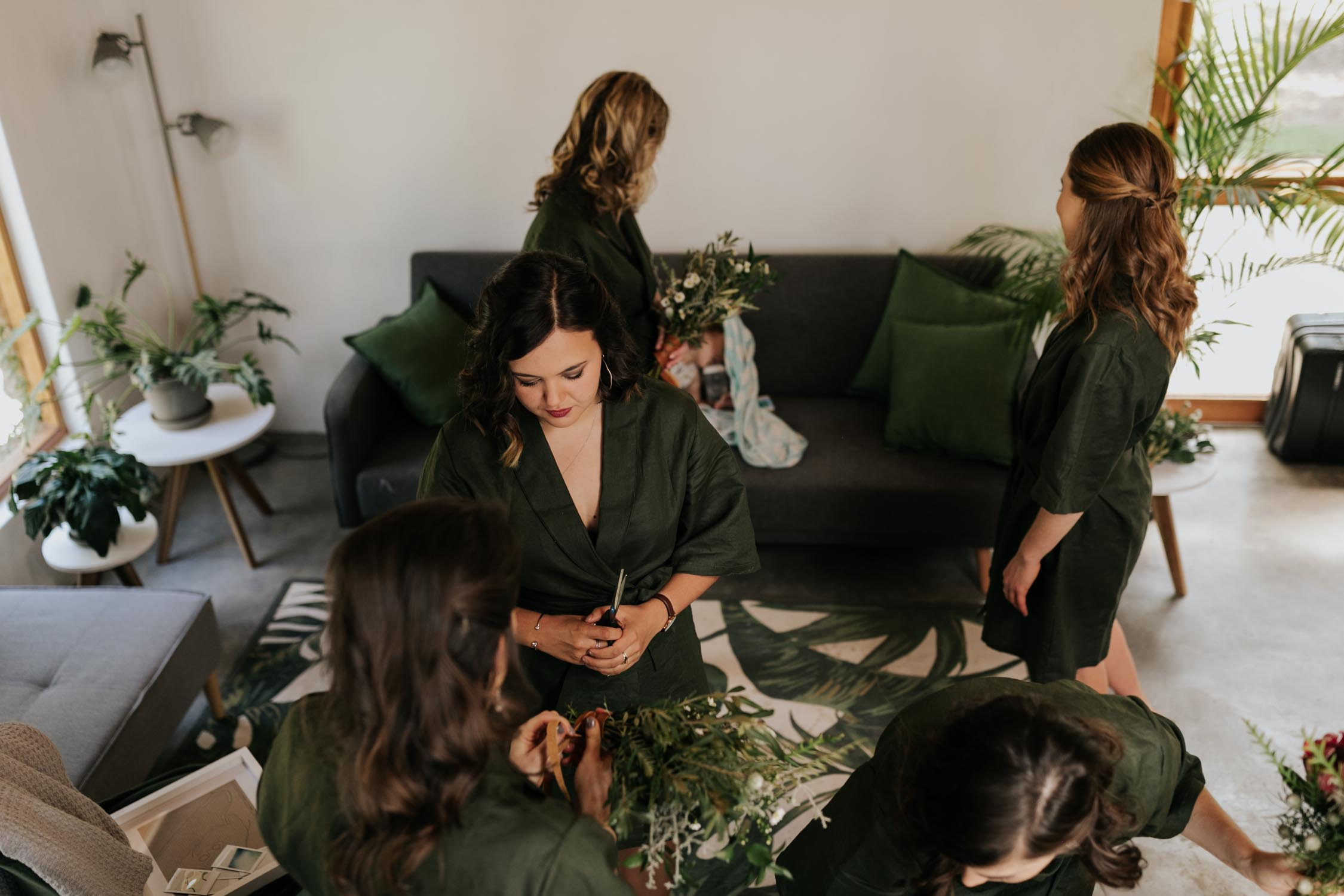 Bridesmaids wearing emerald green dressing gowns make flower crowns for forest wedding