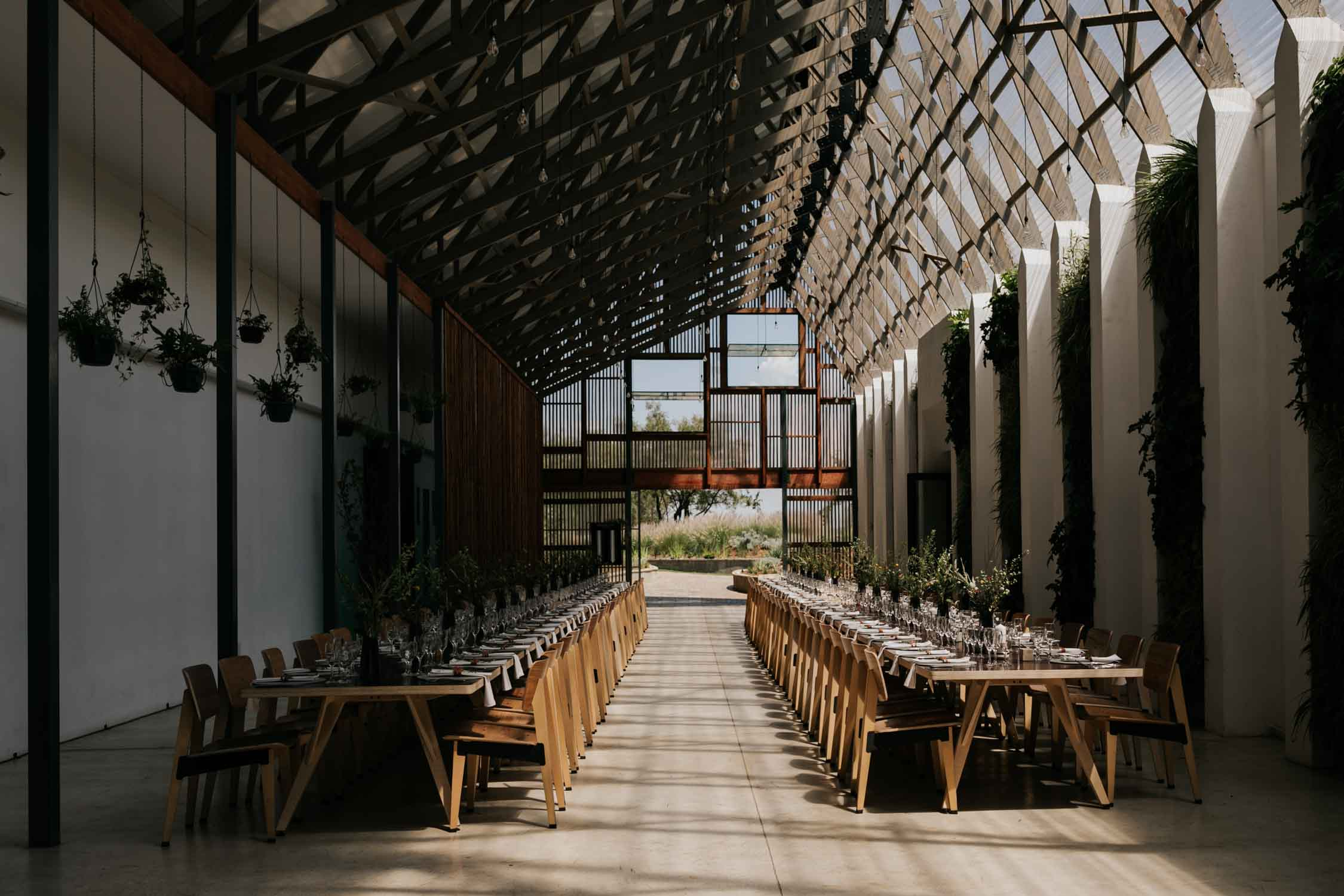 Long tables with industrial wedding decor set for wedding ceremony at Greenhouse Cafe