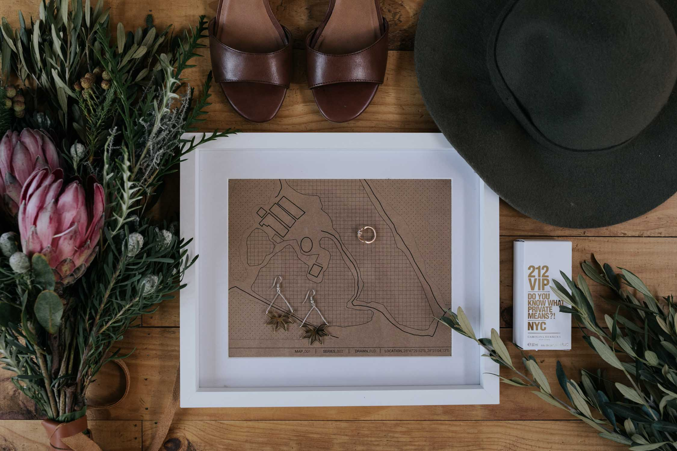 A wedding flat lay of bride's accessories like leather shoes, green felt hat, Protea bouquet, geometric earrings and perfume