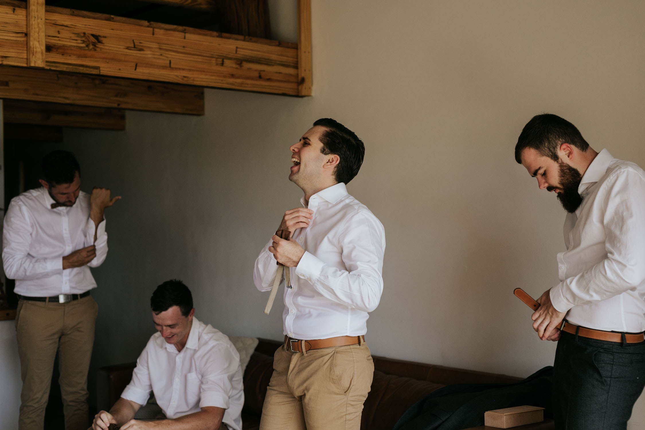 In the moment photo of groomsman laughing wearing beige chinos, a white shirt and leather bowtie, as he gets ready for wedding ceremony