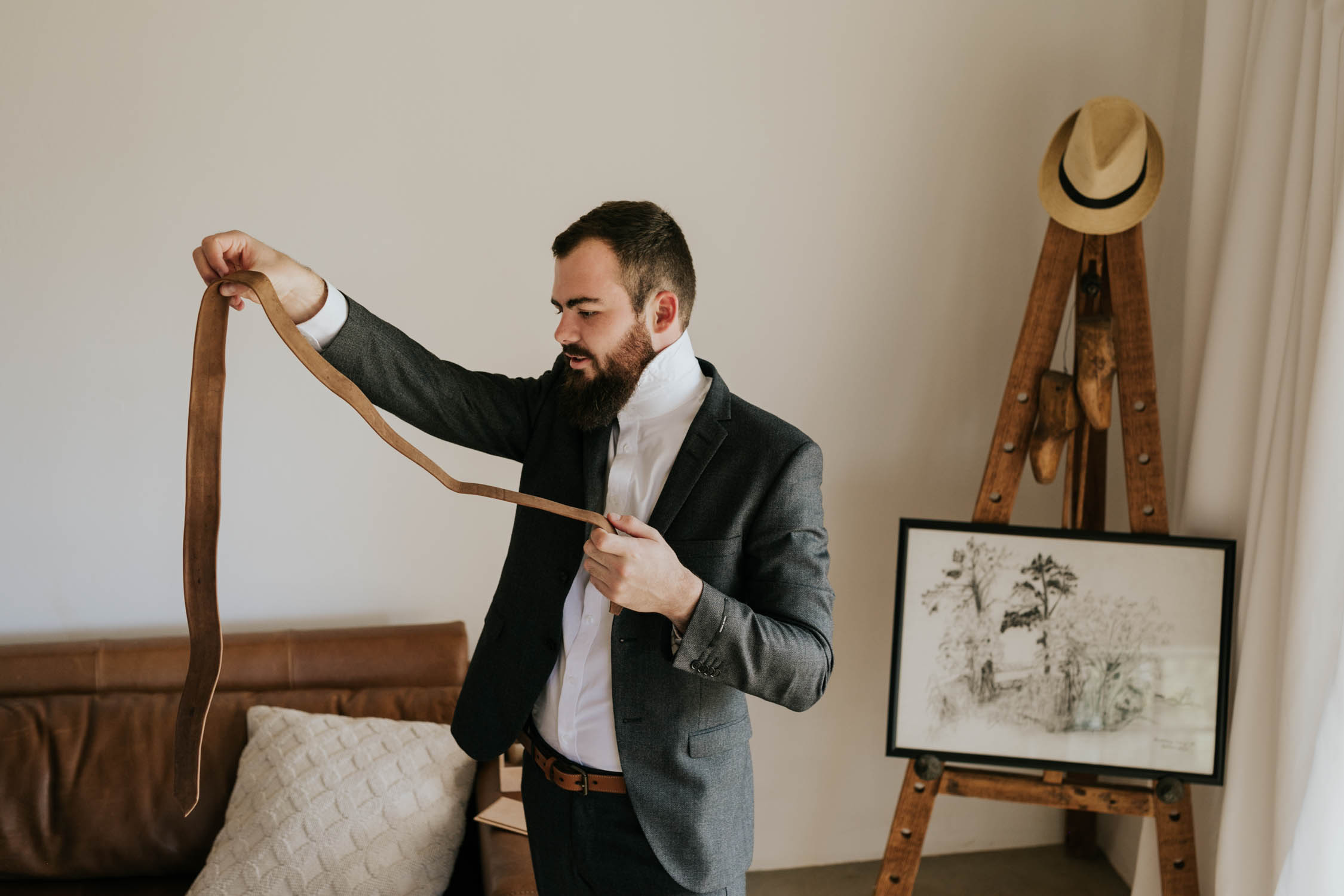 Groom gets dressed for his wedding in a stylish outfit consisting of a grey Tiger of Sweden jacket, leather tie and white shirt