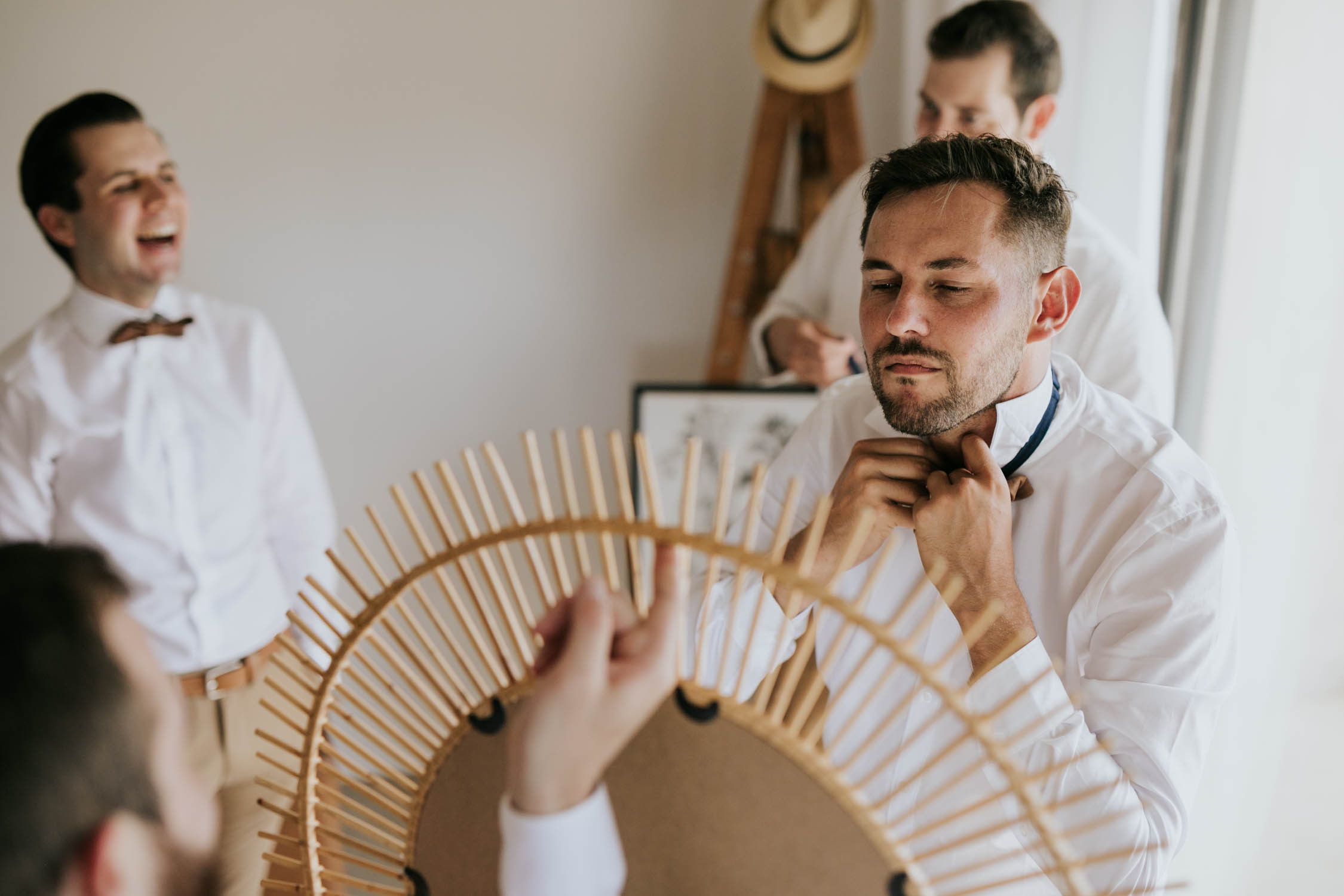 Groomsman looks in a boho mirror and puts on leather bowtie for hipster wedding