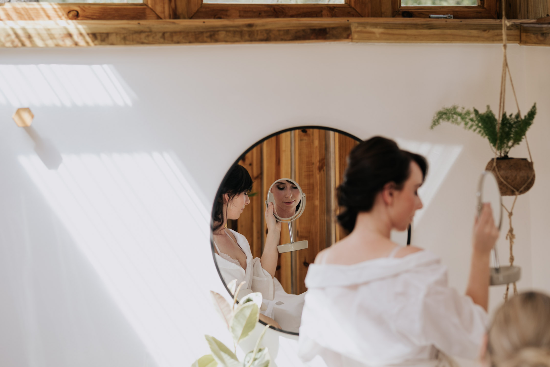 Creative photo of bride's reflection as she looks in the mirror at her bridal hair and makeup at The Greenhouse Cafe Wedding Venue