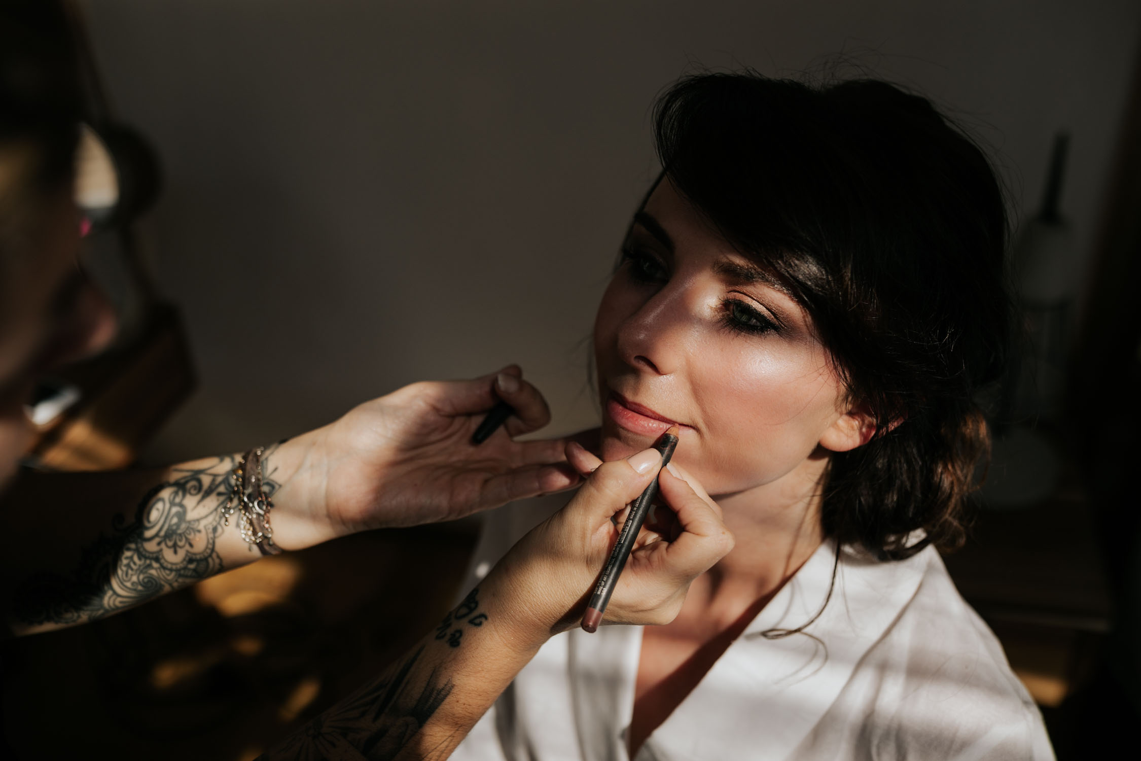 Light shines on bride as makeup artist puts on her lip liner