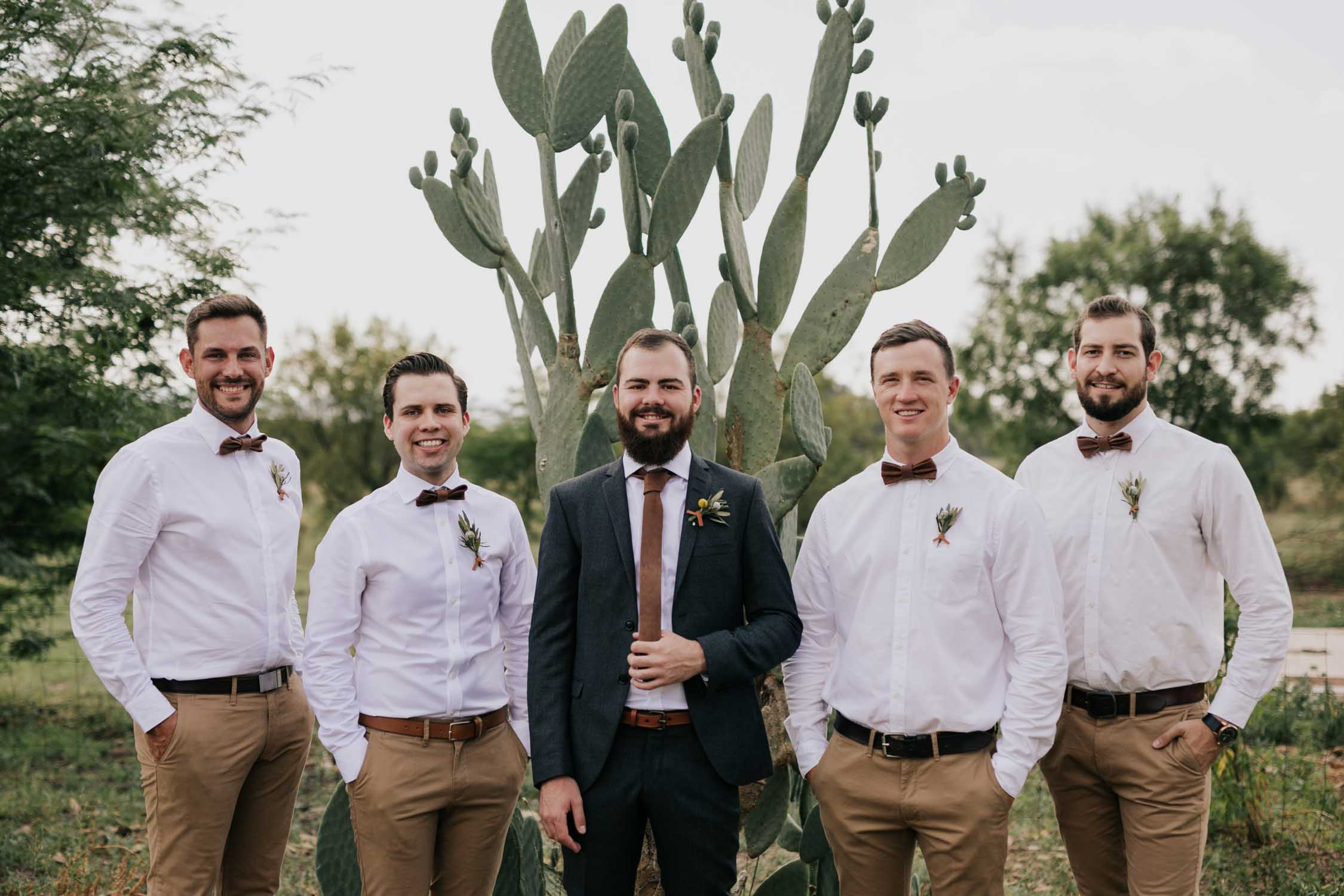 Portrait of hipster groom and groomsmen in front of a cactus plant
