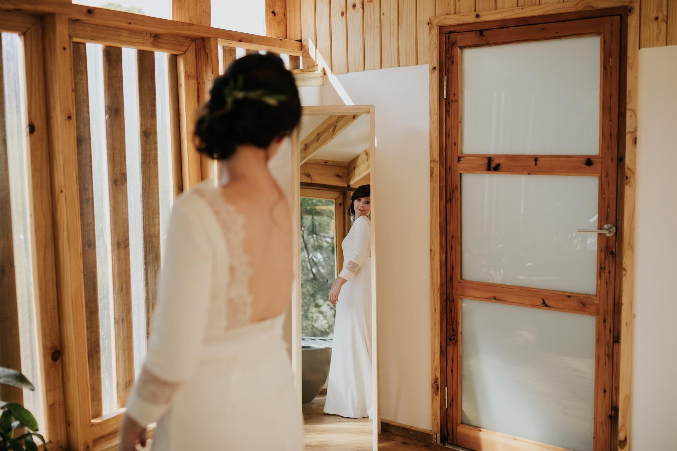 Bride looks in the mirror wearing a simple lace backless wedding dress with three quarter sleeves