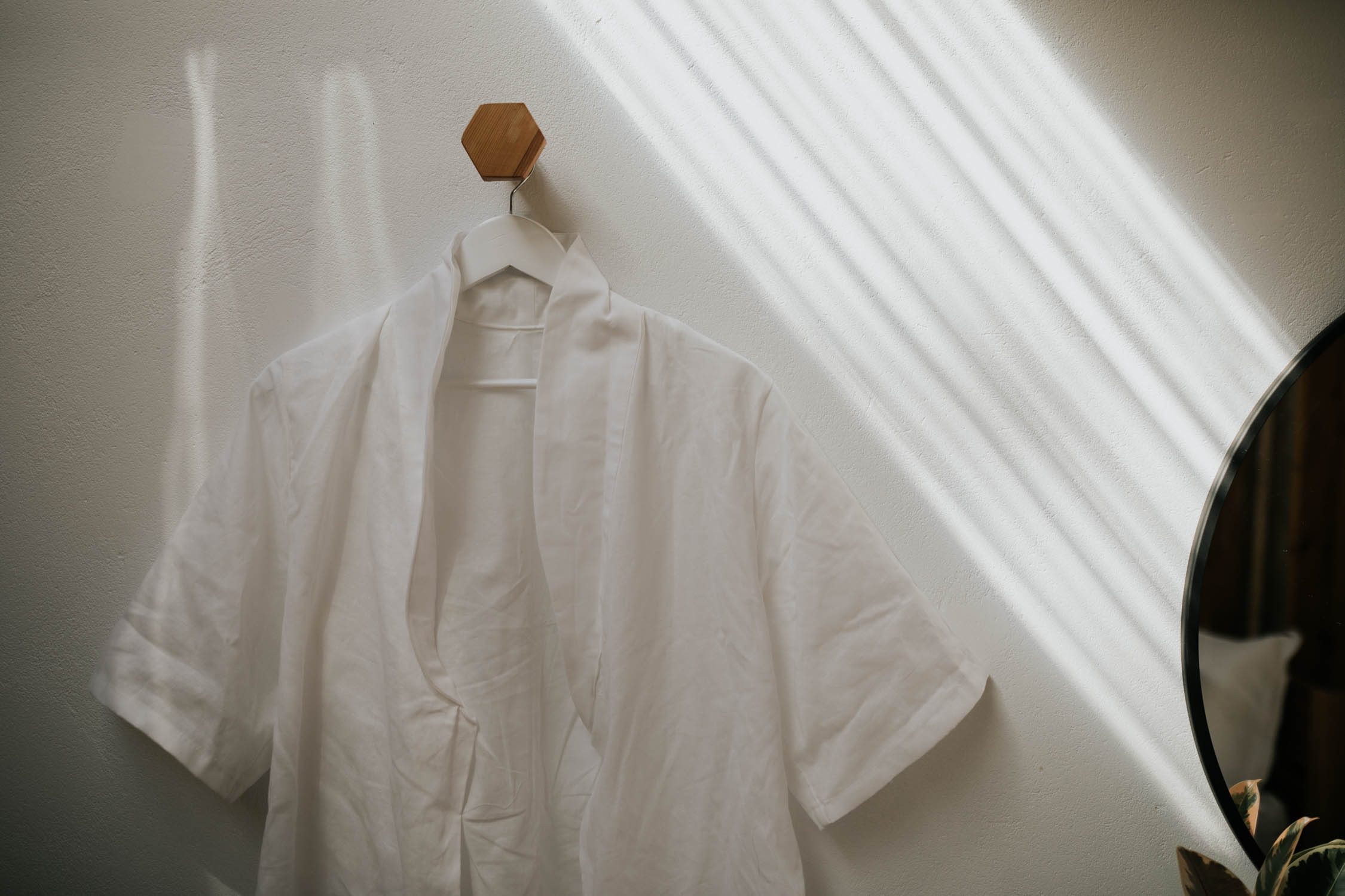 Bride's white linen gown hangs on wooden geometric hook