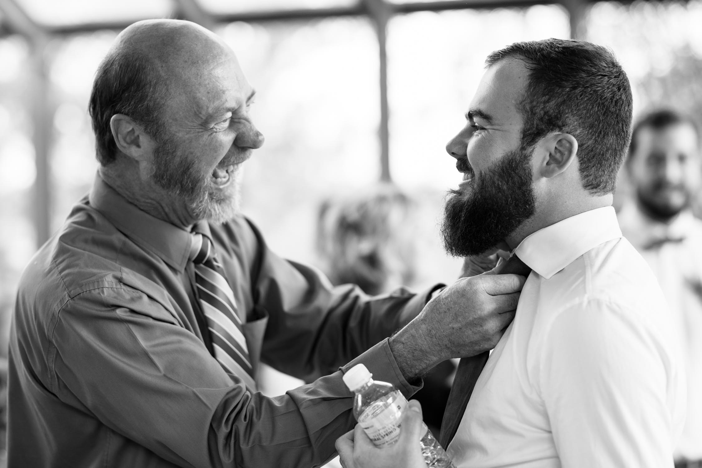 Candid moment taken by Vancouver Wedding Photographer of guest helping groom with his brown leather tie