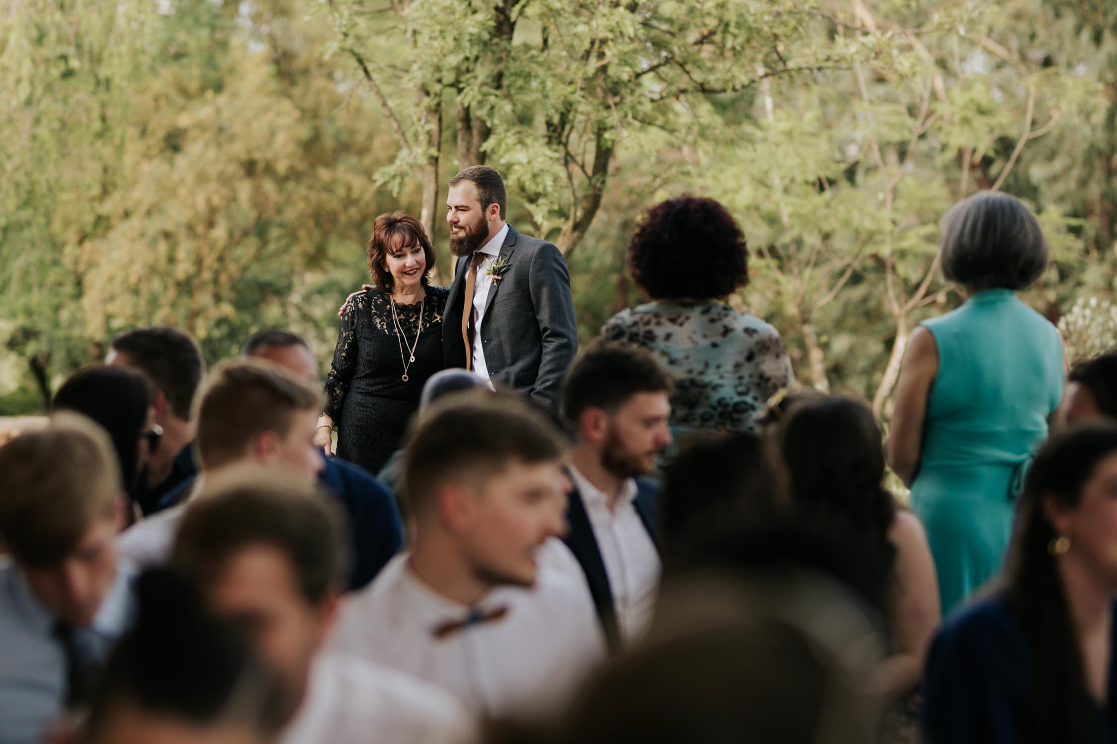 Photo journalistic moment of groom greeting his mother in law at forest wedding ceremony