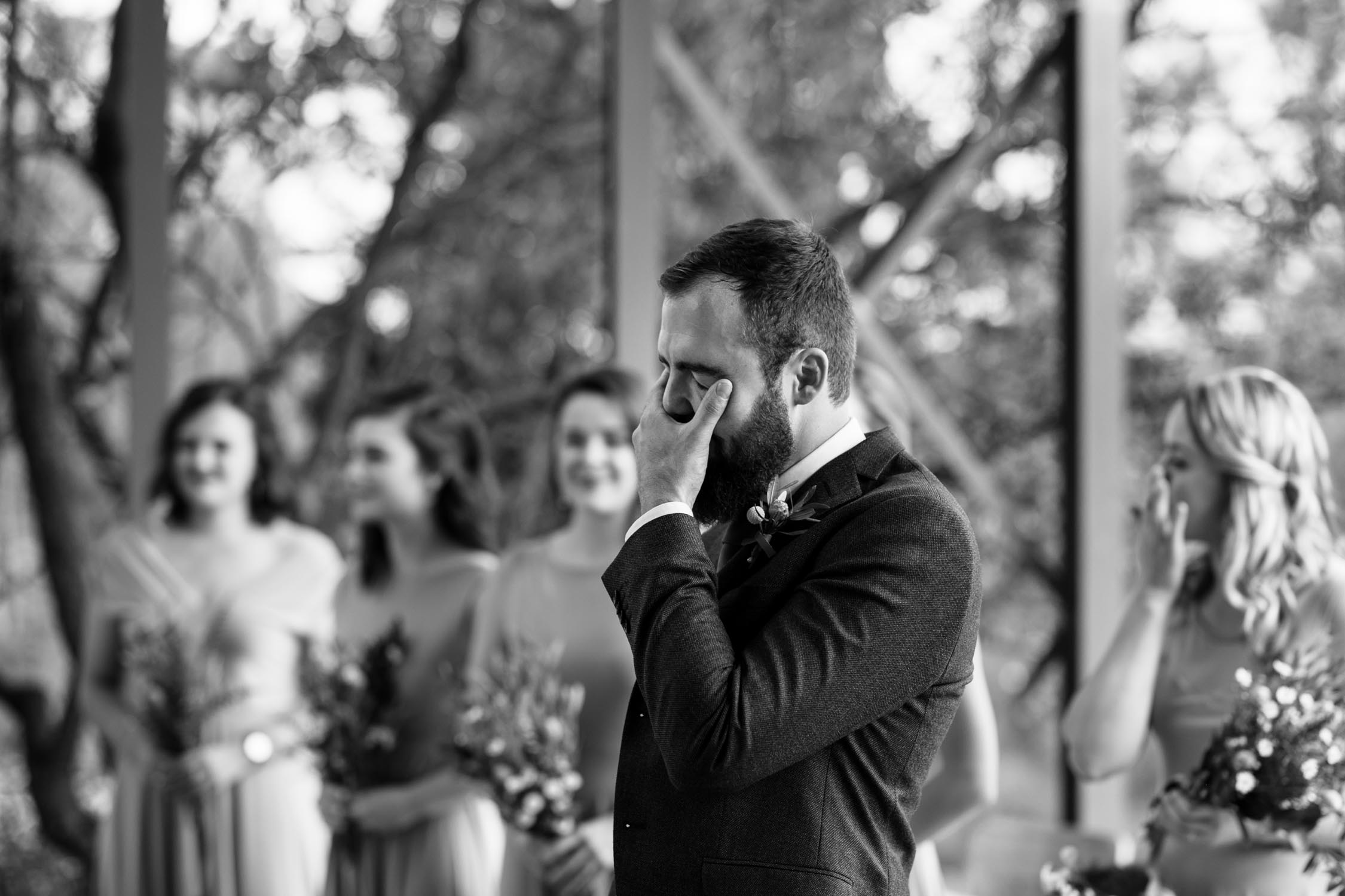 Groom's emotional reaction as he watches his bride walk down the aisle