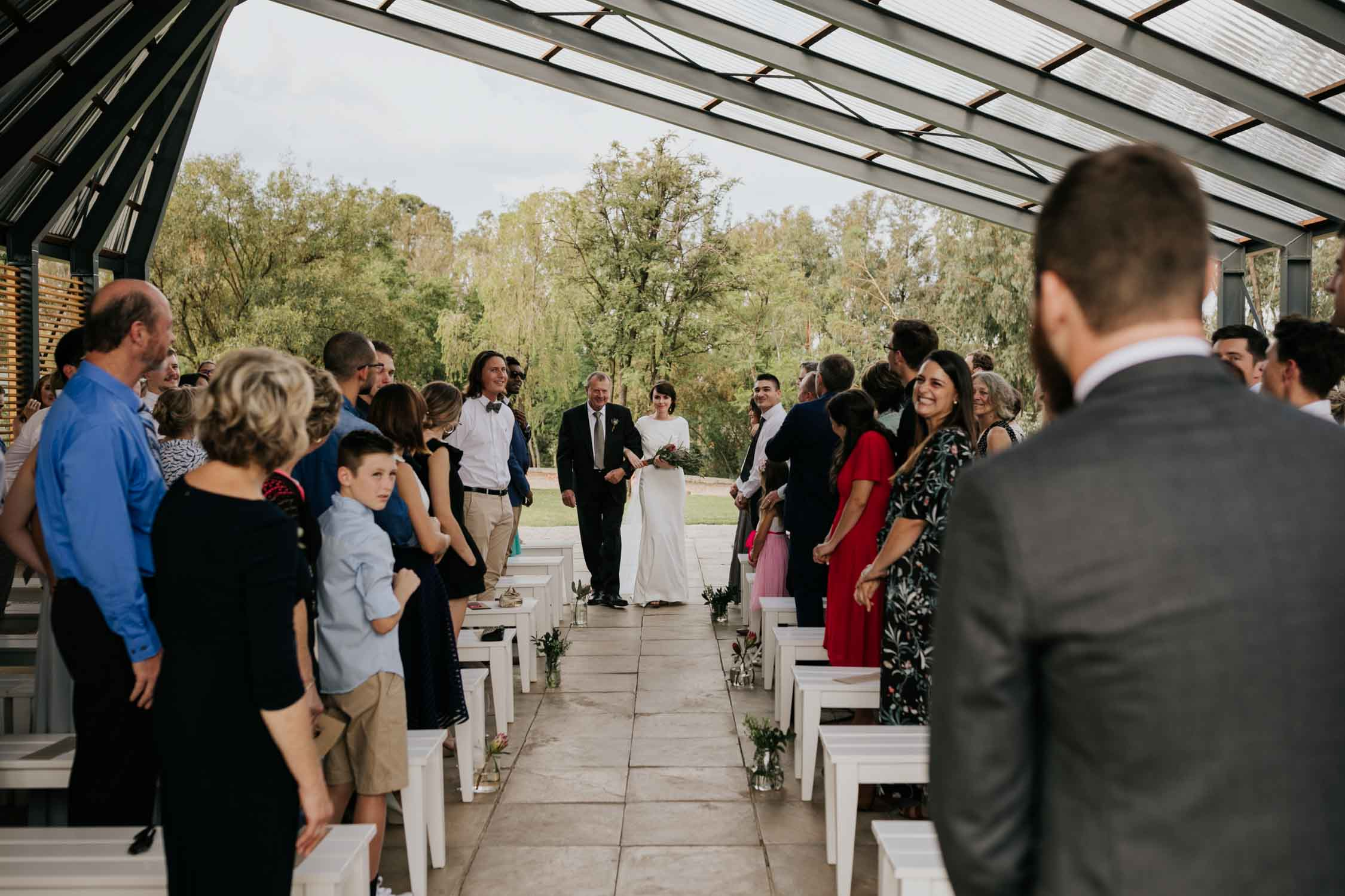 Modern simple bride walks down the aisle with her father in outdoor midcentury wedding ceremony venue