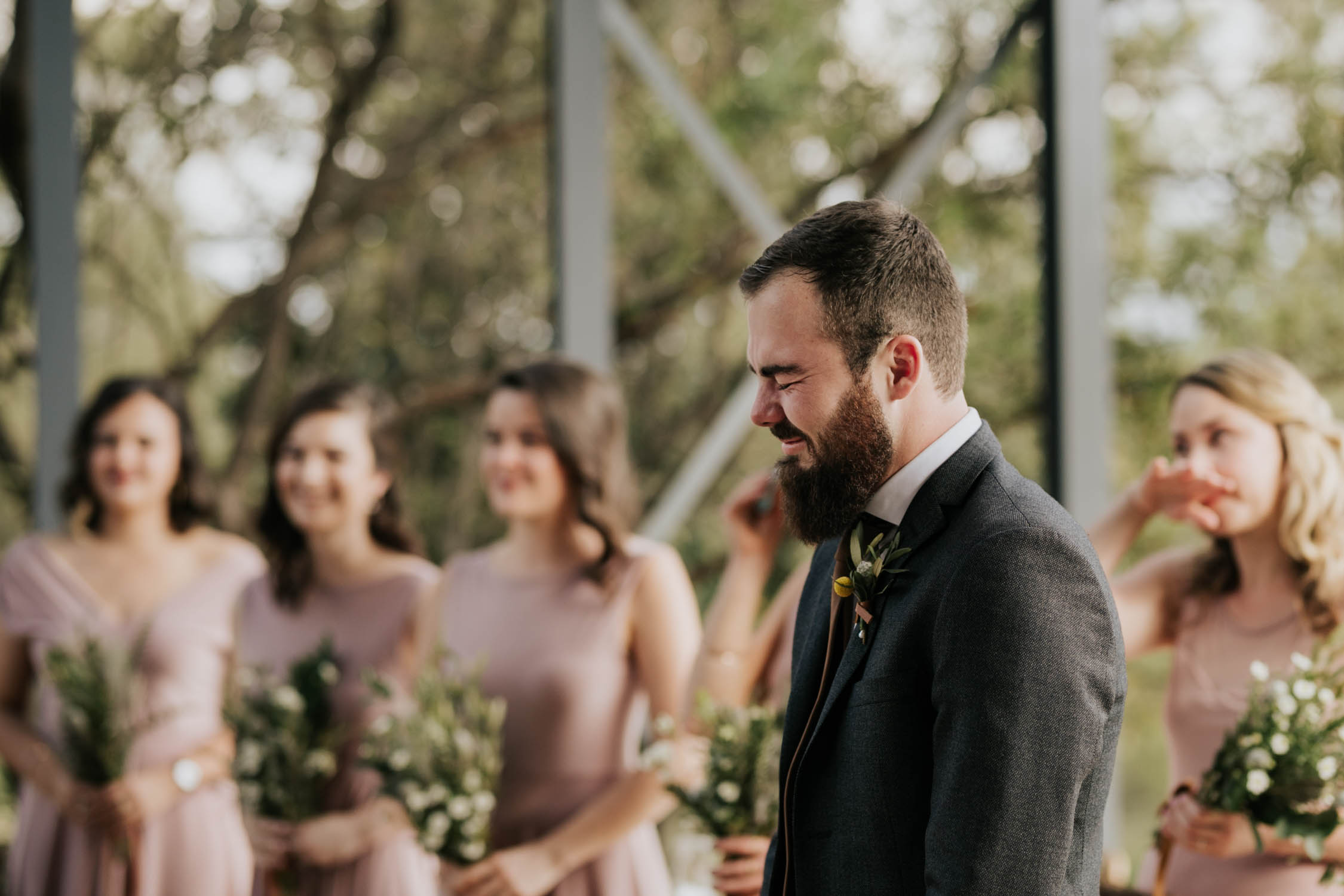 Groom's emotional reaction as he watches his bride walk down the aisle taken by candid Vancouver Wedding Photographer