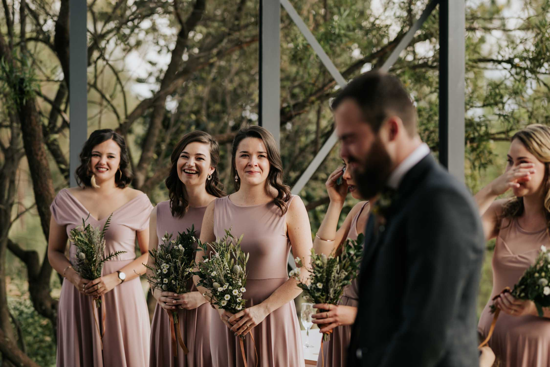 Bridesmaids wearing dusty pink dresses watch groom's emotional cry as he watches bride walk down aisle
