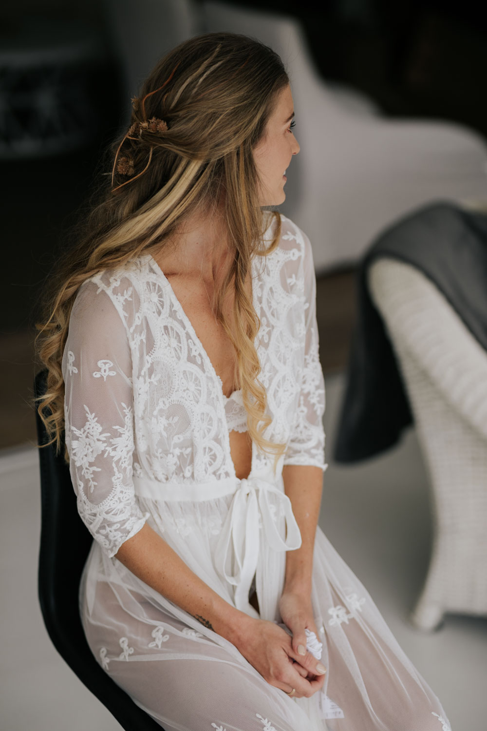 Beautiful boho bride in lace gown getting her hair done on her wedding day