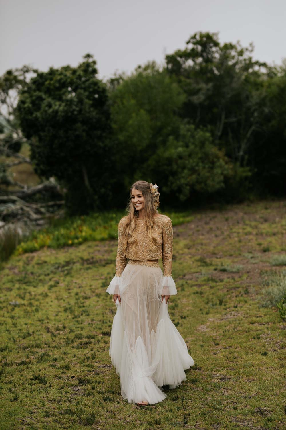 Boho bride with long curly blonde hair wears two piece gold and cream long sleeve wedding dress and feathers and plait in her hair