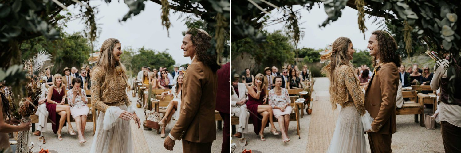 Emotional wedding moment when couple greet each other at the top of the aisle at boho wedding ceremony
