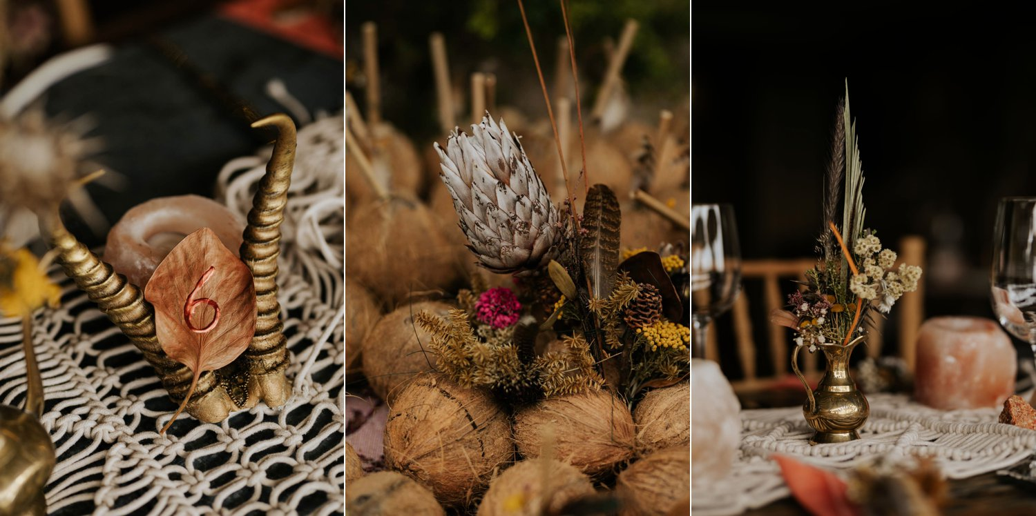 Boho inspired wedding decor of rustic wooden chairs, woven macrame table runners, feather and dried flower arrangements in brass and copper pots, skull table numbers, gemstones and Bali Wicker Peacock Chairs