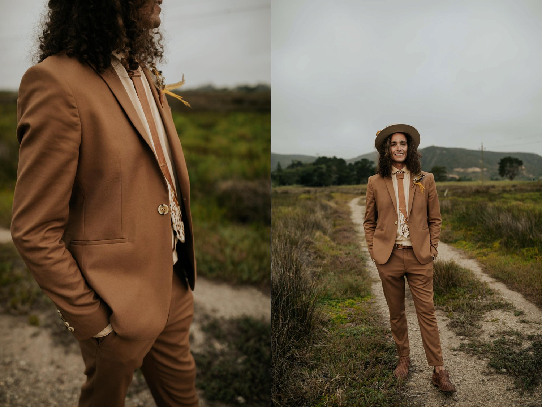 Long curly hair groom wears brown suite, beige shirt, brown Nguni cowhide tie, felt hat and foraged dried flowers and feather boutineer