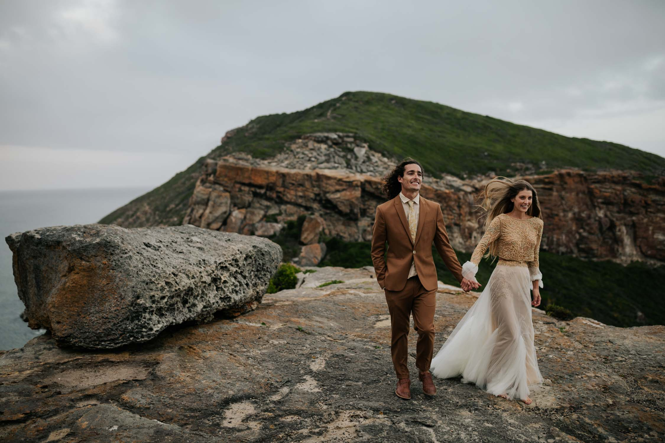 Photo by Vancouver Photographer of groom wearing brown suite, beige shirt, and felt hat walks with bride wearing gypsy wedding dress with flared long sleeves, sheer skirt and gold detailed top on top of cliff