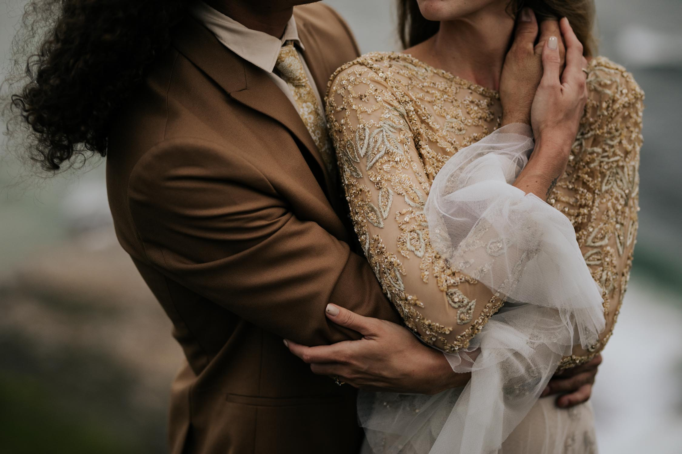 Adventure Wedding Photo Session by Vancouver Photographer of groom wearing brown suite, beige shirt, and felt hat walks with bride wearing gypsy wedding dress with flared long sleeves, sheer skirt and gold detailed top on edge of cliff
