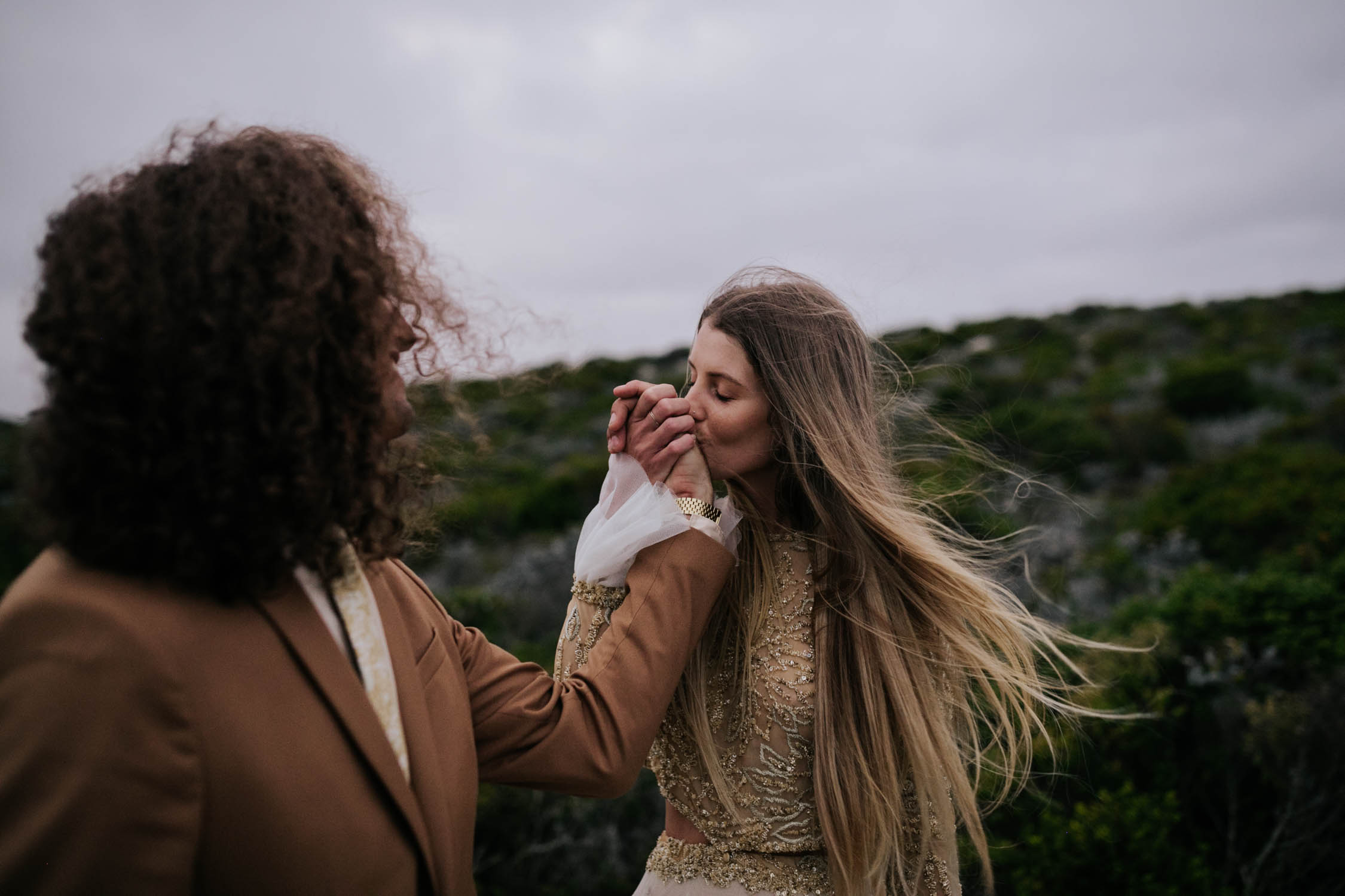 Amazing photo of bride kissing grooms hand with the wind making her hair wild and crazy
