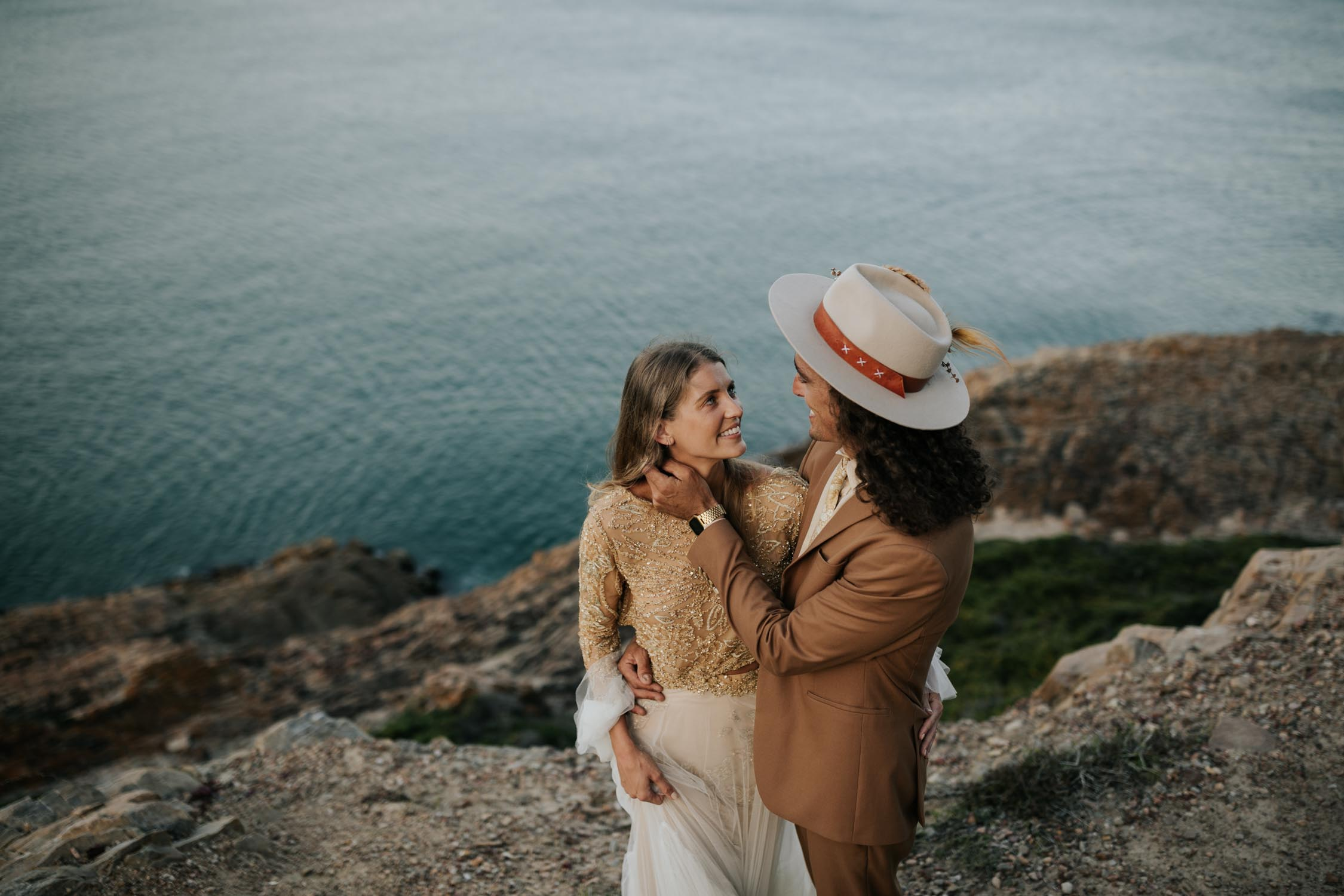 Groom wearing brown suite, beige shirt, brown Nguni cowhide tie, felt hat and foraged dried flowers holds bride wearing gypsy wedding dress with flared long sleeves, sheer skirt and gold detailed top at the ocean