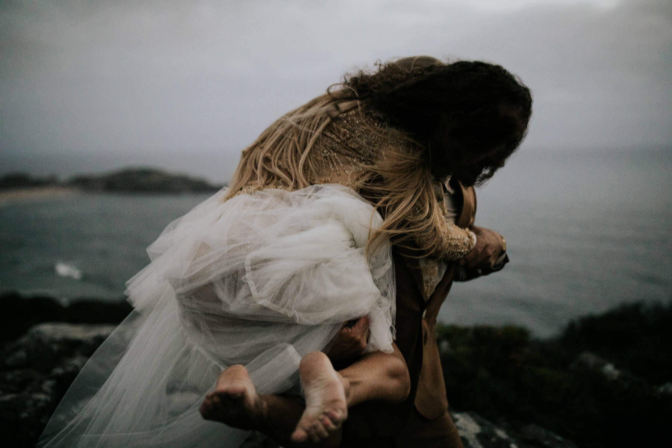 Groom carries barefoot bride on the cliffs overlooking the ocean at dusk