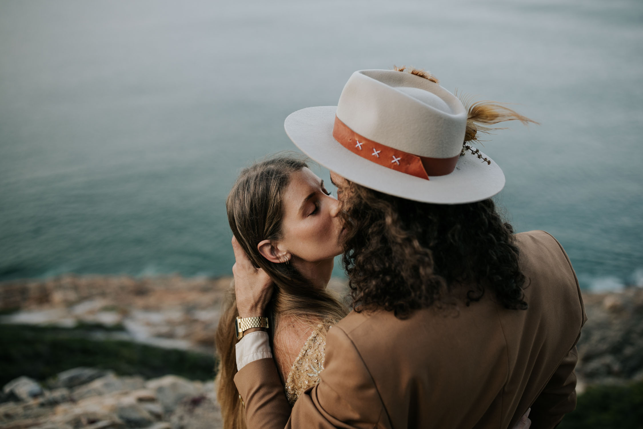 Groom wearing brown suite, beige shirt and felt hat kisses beautiful bride wearing gypsy wedding dress with flared long sleeves, sheer skirt and gold detailed top at the top on an ocean cliff