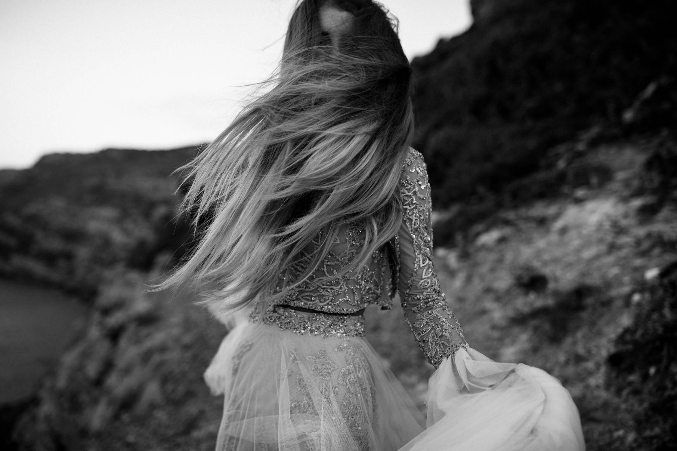 Boho bride wears gypsy wedding dress with flared long sleeves, sheer skirt and gold detailed top shakes her long hair in the wind