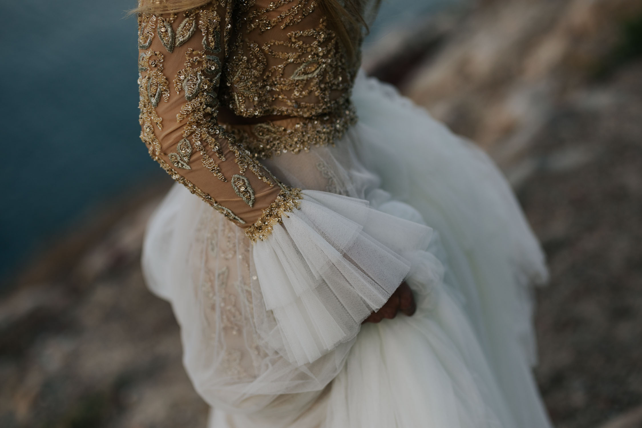 Boho bride wears gypsy wedding dress with flared long sleeves, sheer skirt and gold detailed top