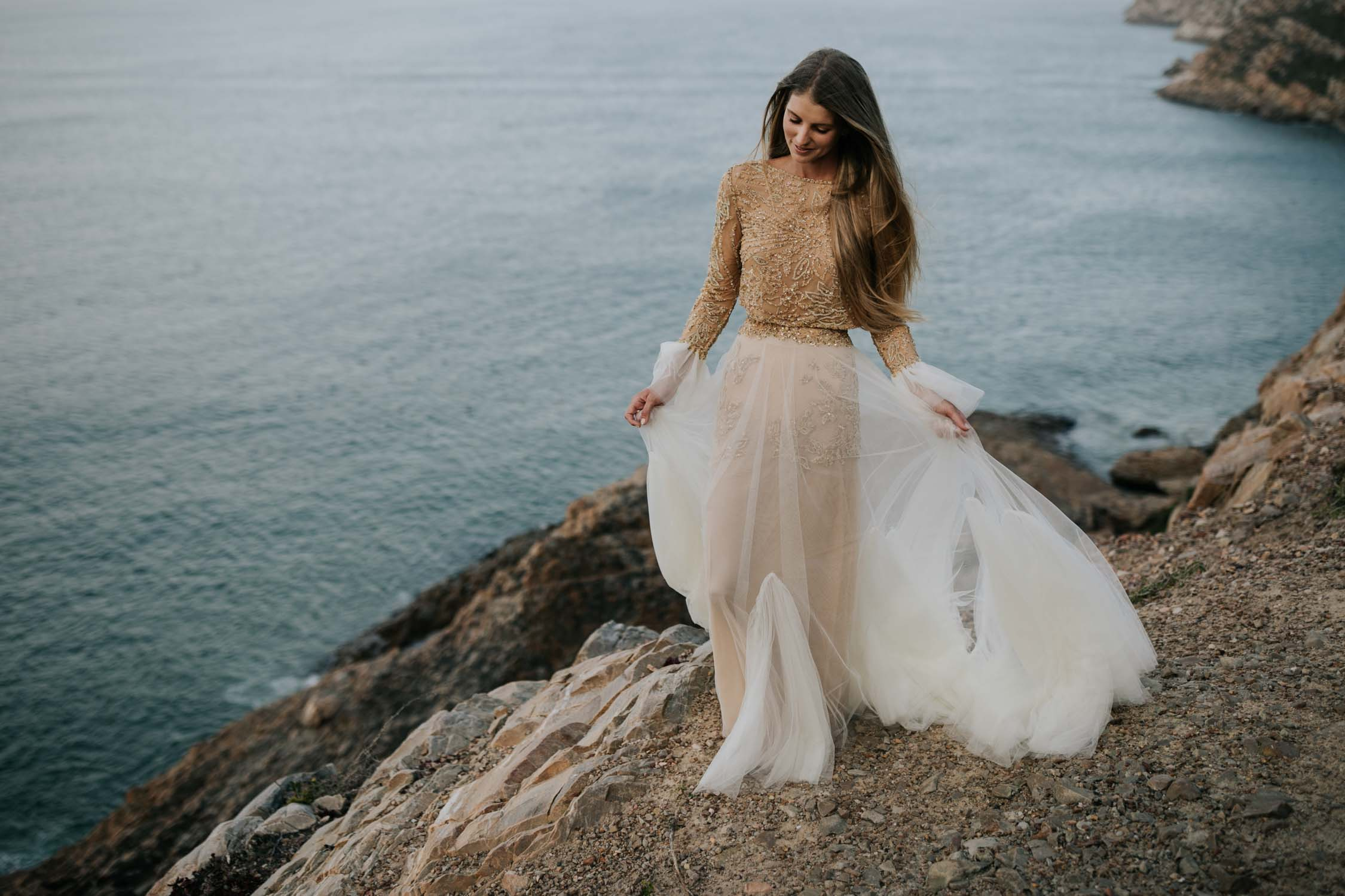 Boho bride wears gypsy wedding dress with flared long sleeves, sheer skirt and gold detailed top on top of a cliff with epic wild ocean below